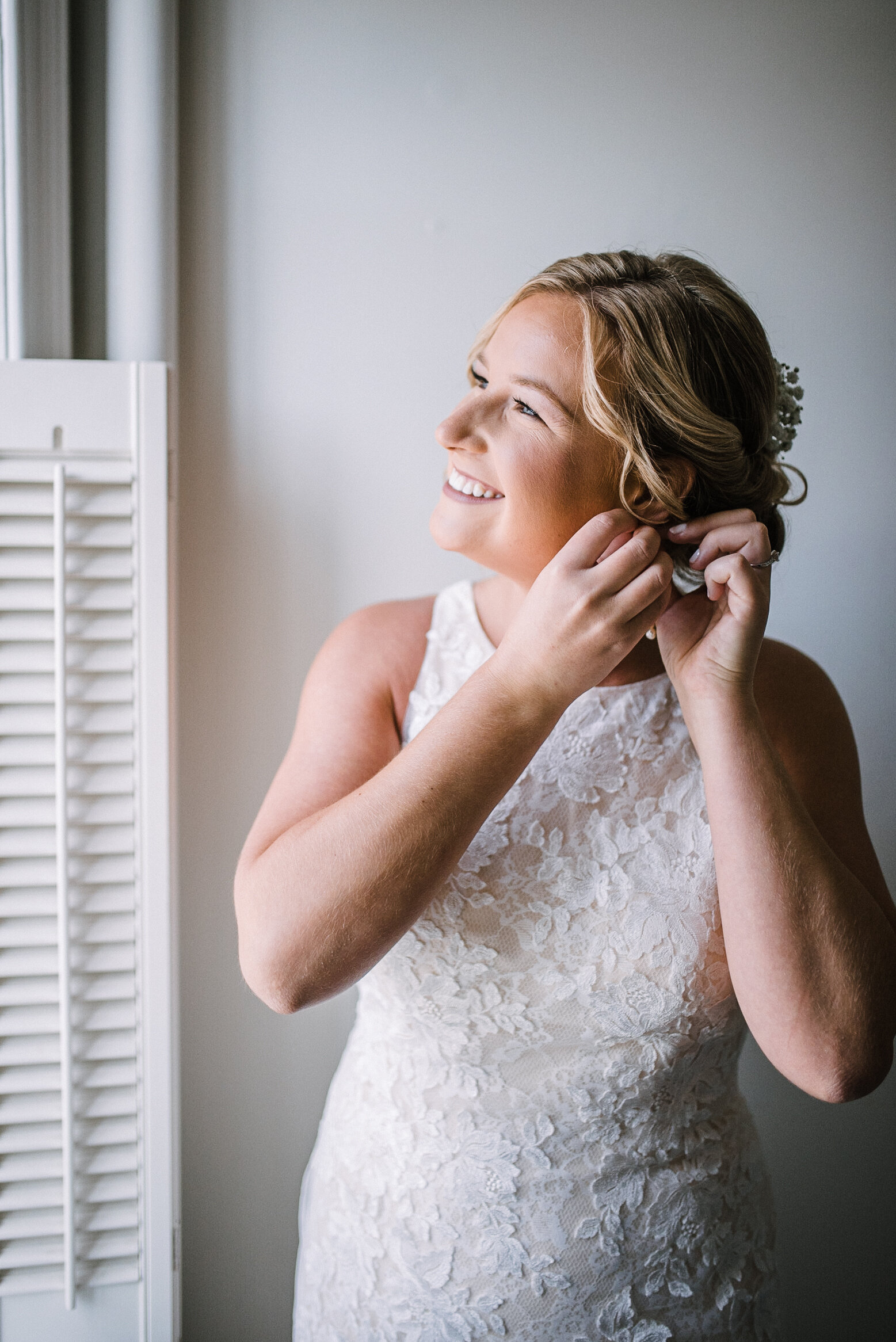 Bride putting on earrings at Birkby House