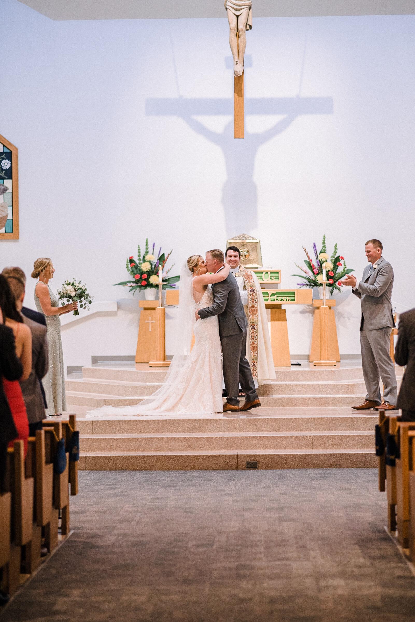 Bride and groom kissing at the altar at St. Joseph Catholic Church