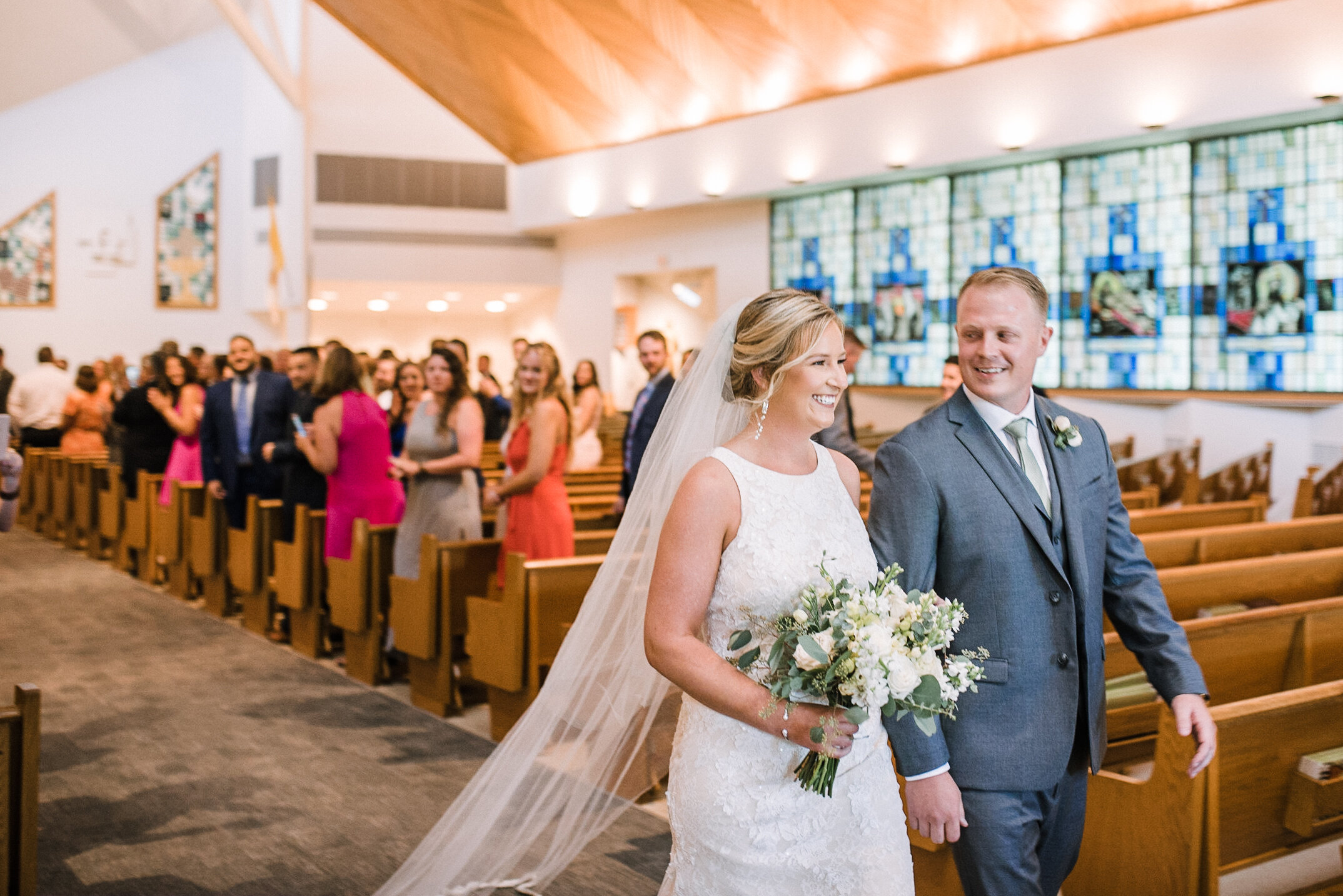 Bride and groom smiling as they walk down the aisle at St. Joseph Catholic Church