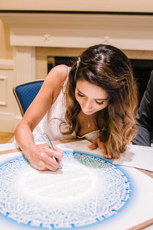 bride signing ketubah at The Winslow