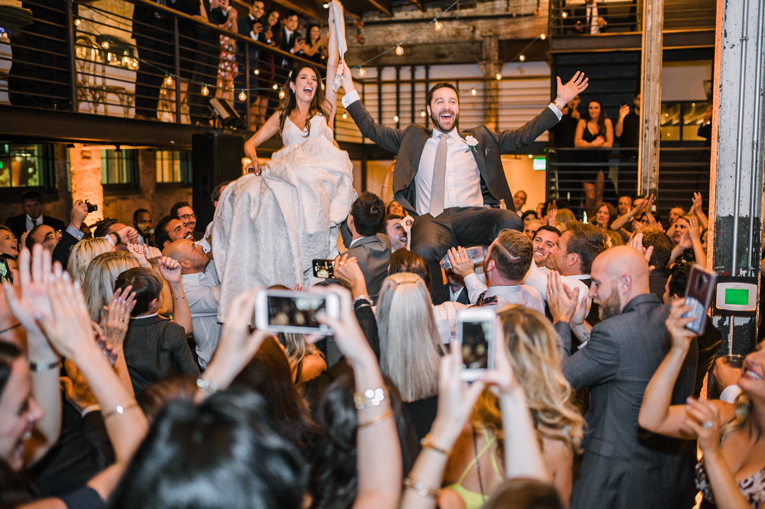 bride and groom being carried by guests during reception at The Winslow