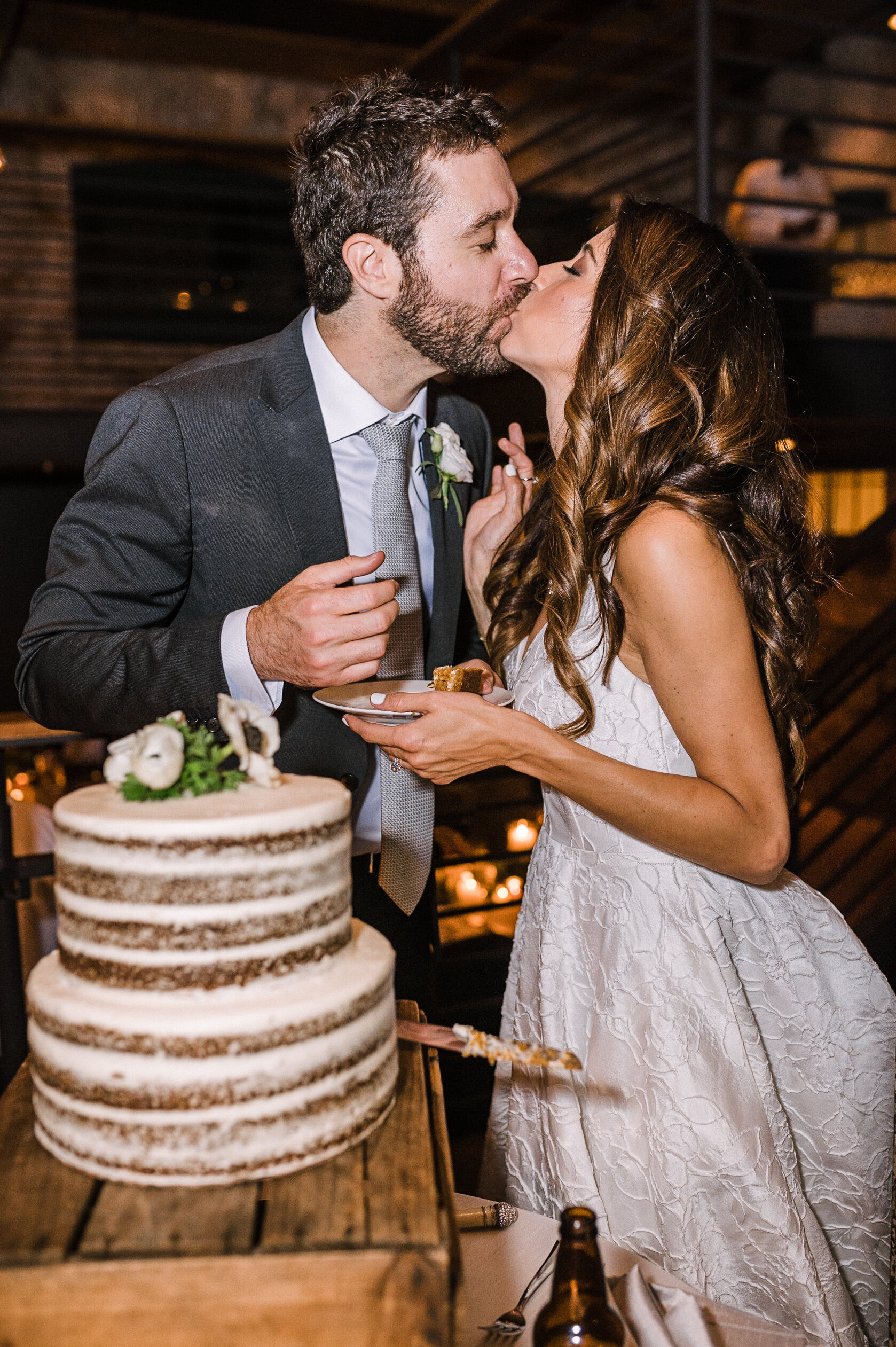 bride and groom kissing as they cut cake at The Winslow