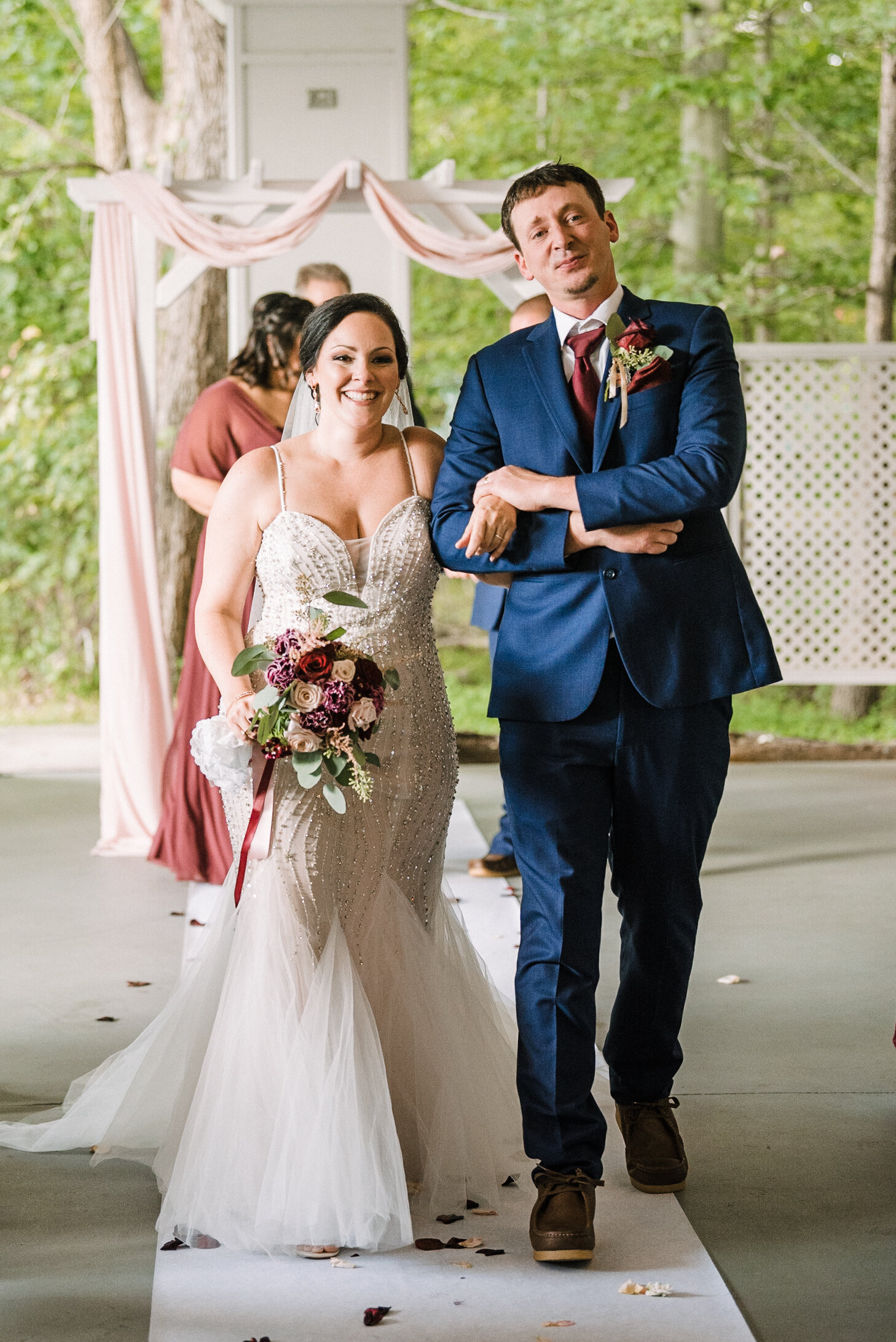 bride and groom smiling as they walk up the aisle at Westfields Golf Club