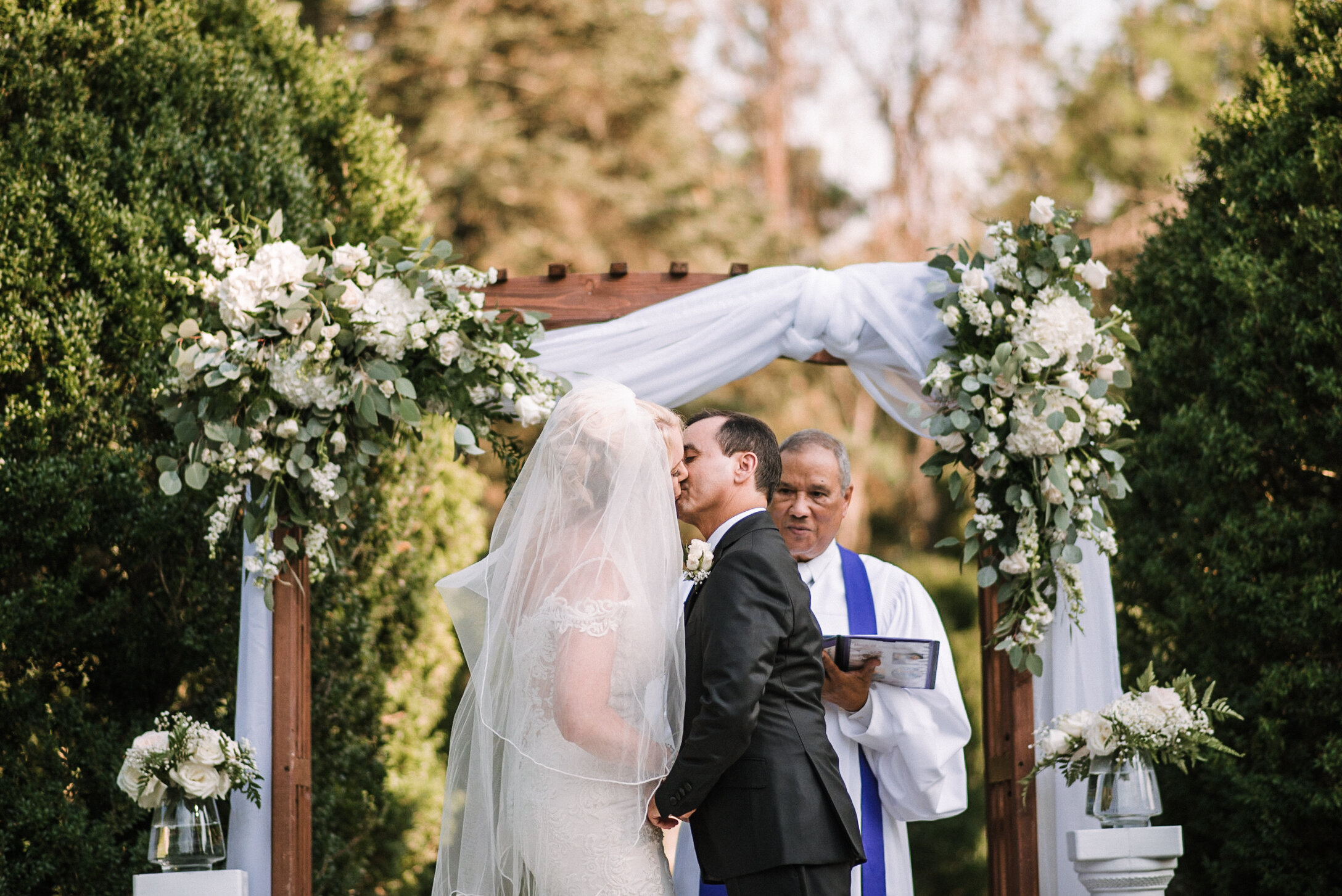 bride and groom kissing during ceremony at Rust Manor House