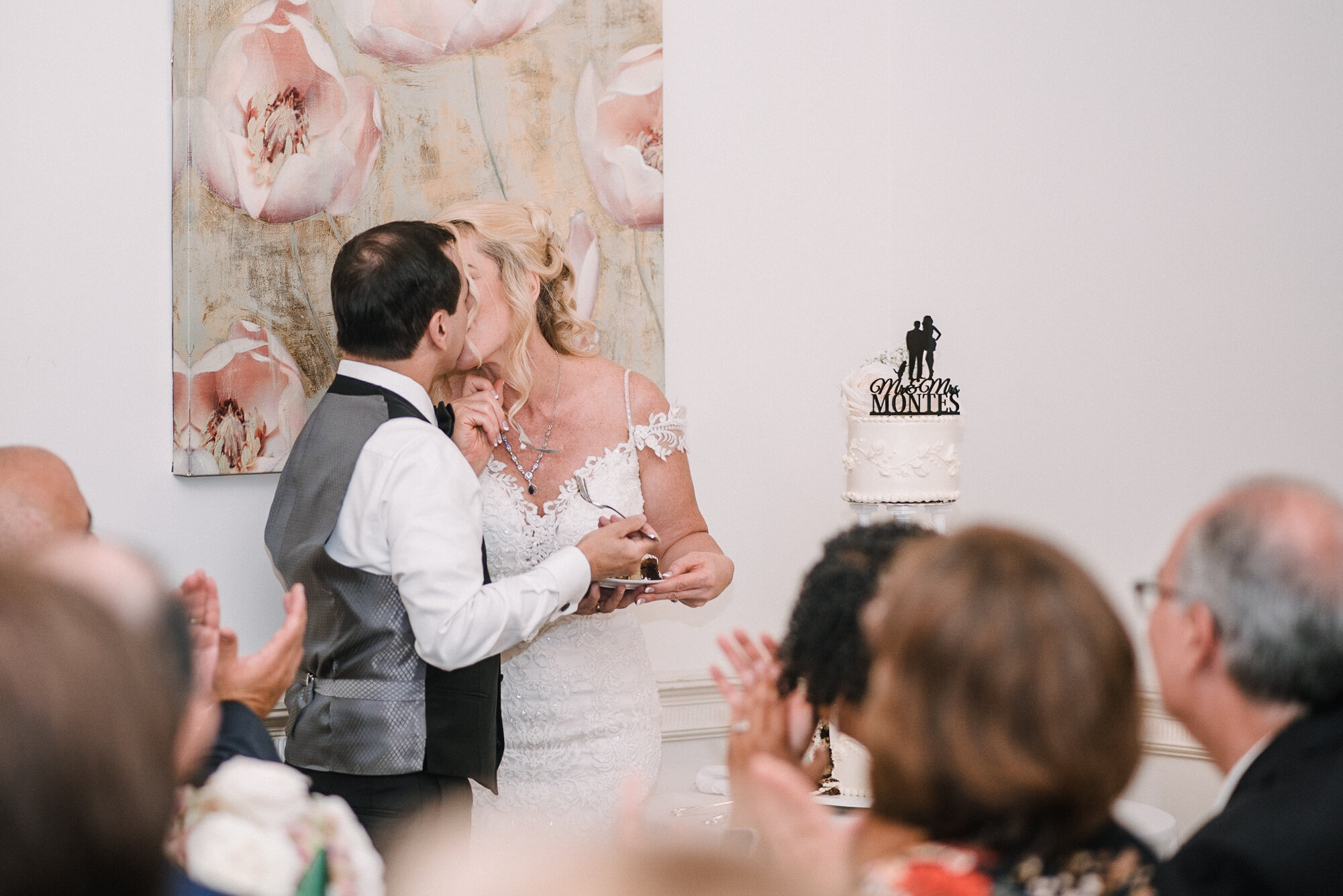 bride and groom kissing as they cut the cake at Rust Manor House
