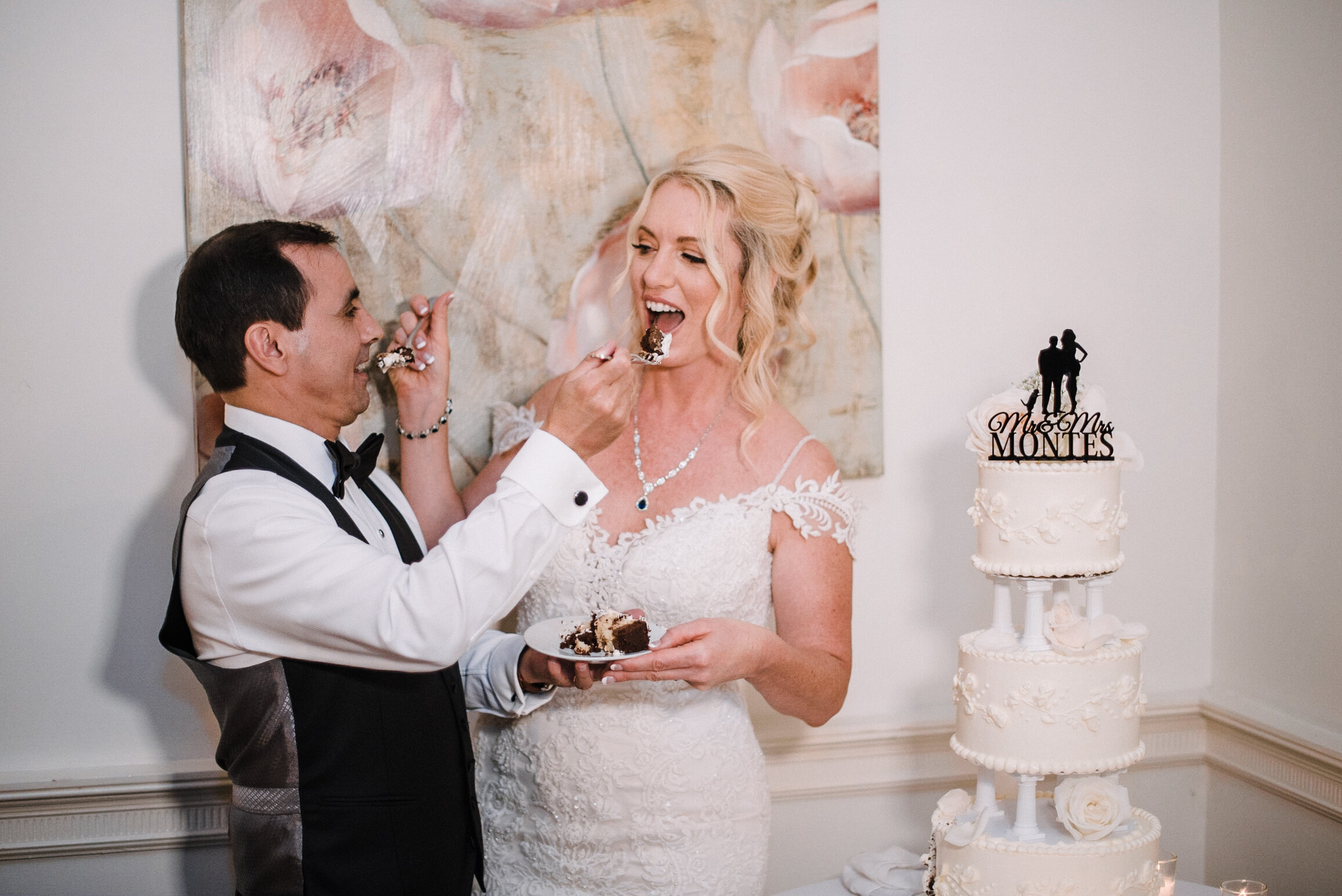 bride and groom eating cake at reception at Rust Manor House