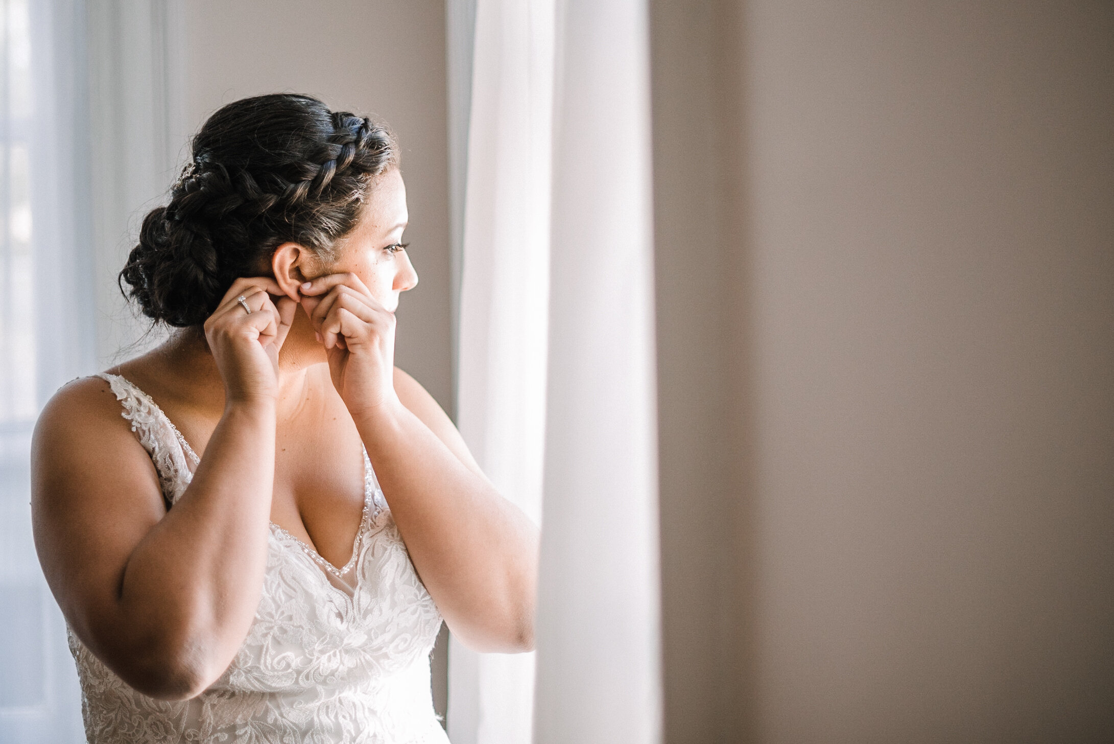 bride putting on earrings at The Inn at Vint Hill