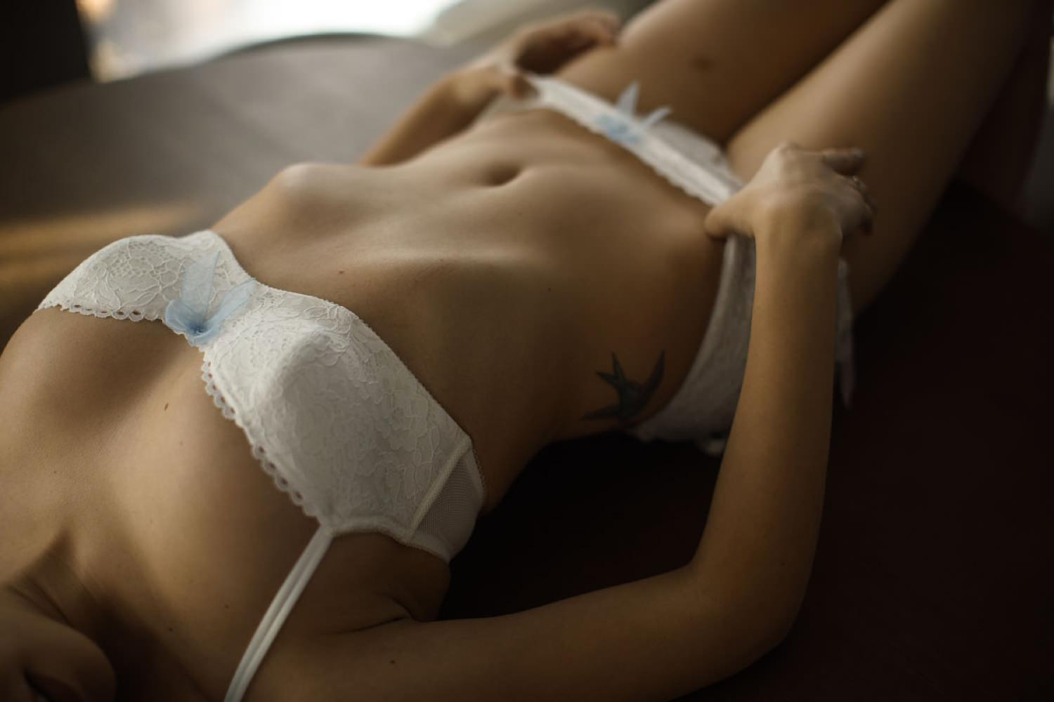 lady shows off her tattoos during boudoir session