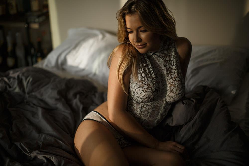 LA boudoir model sitting on bed