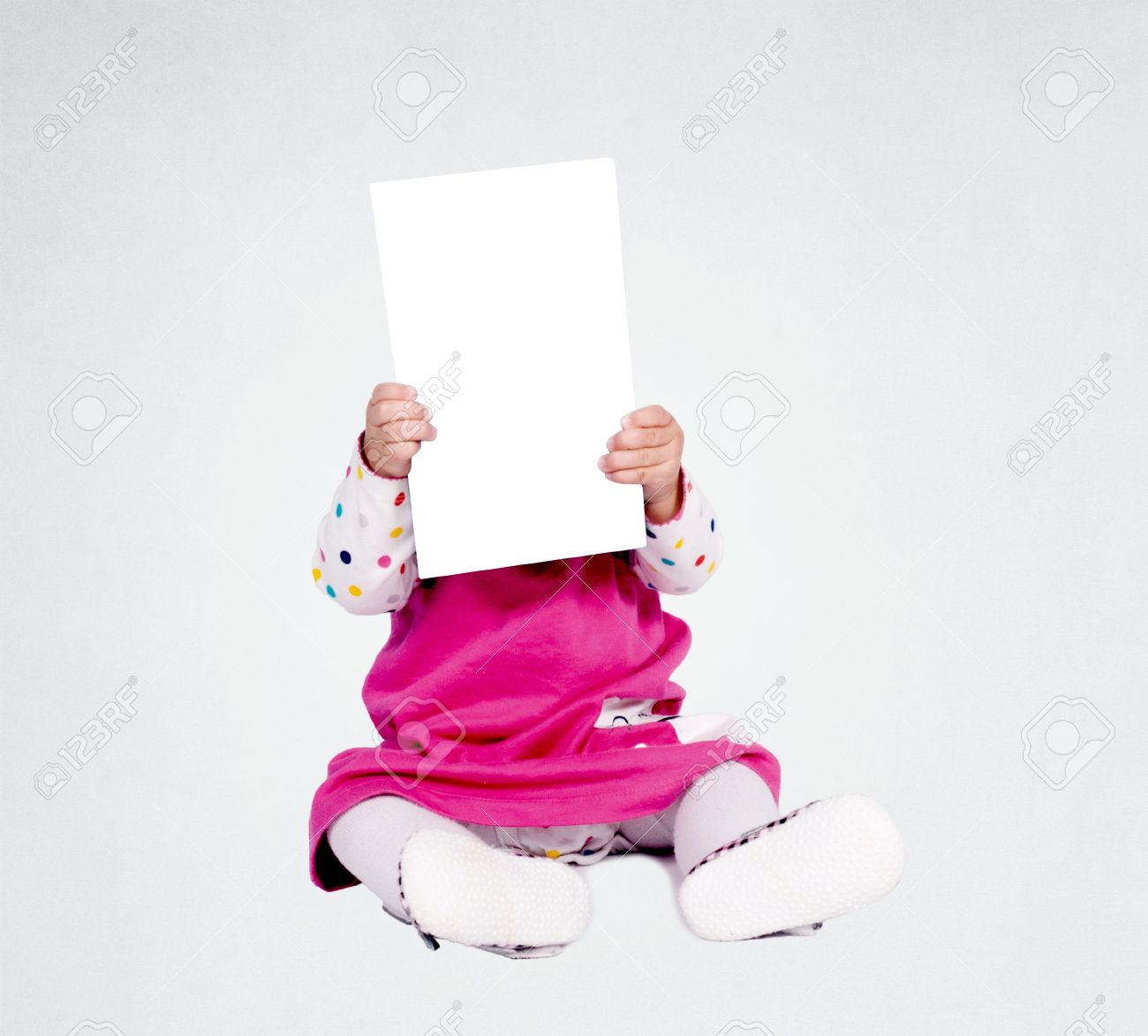 20591707-little-baby-girl-holding-blank-paper-over-her-head.jpg