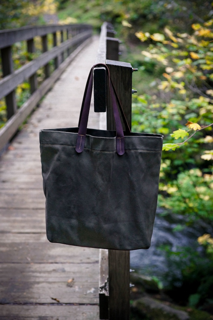 The Private Reserve Tote is a classic shoulder bag featuring hand worked leather handles and interior leather slip pouch.