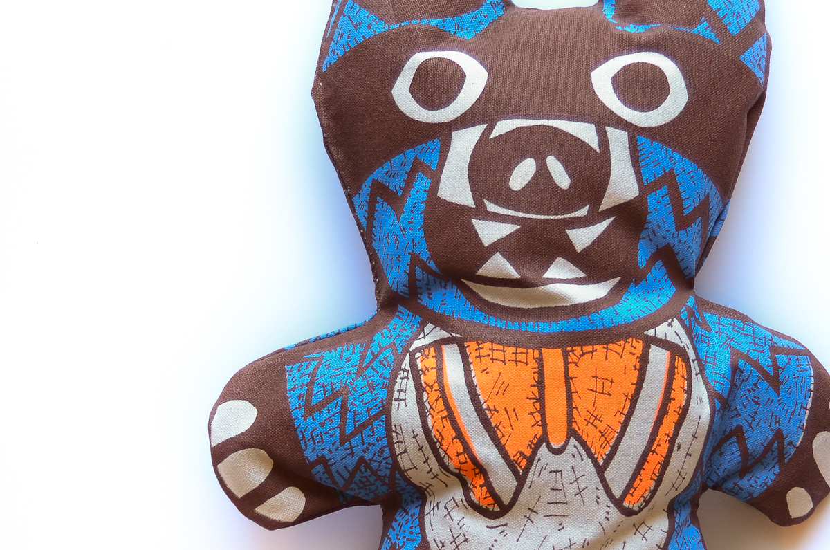 "Mapache Bear, 2014; Hand-sewn Plush Doll, screenprinted on 12oz canvas stuffed with washable stuffing; 18"" x 10"" x 4""; Edition of 10"