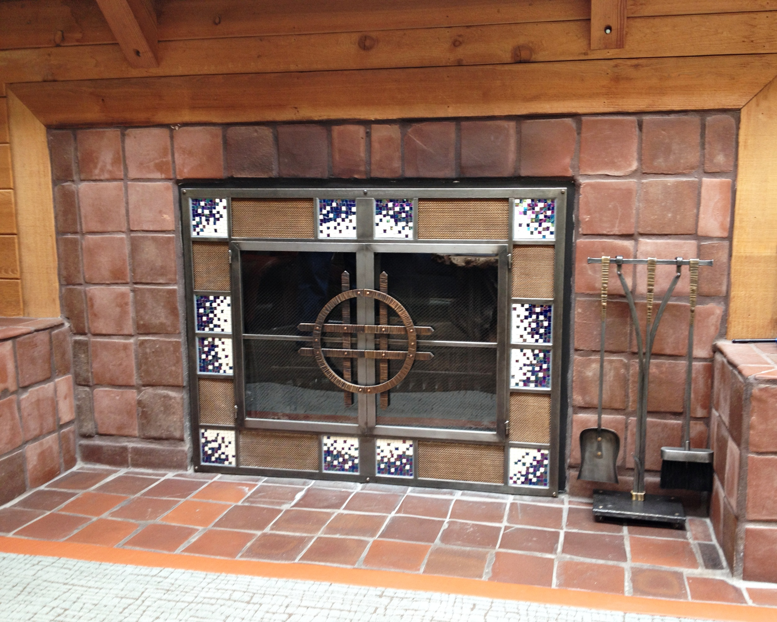 Mosaic Firescreen with forged bronze handles and forged bronze fireplace tool set by Phoenix Handcraft.