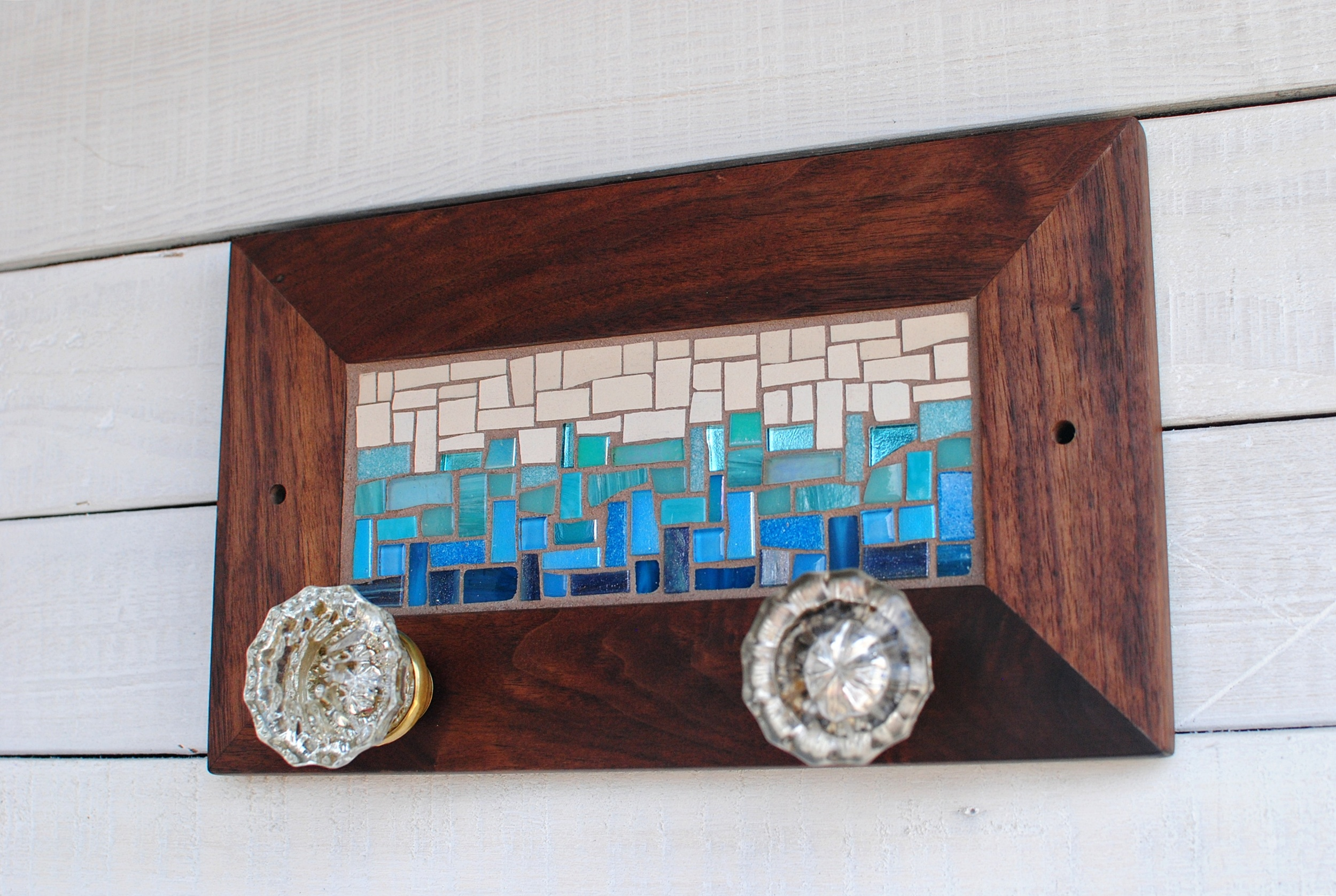 Custom mosaic coat rack in blue and tan with vintage door knobs for hooks