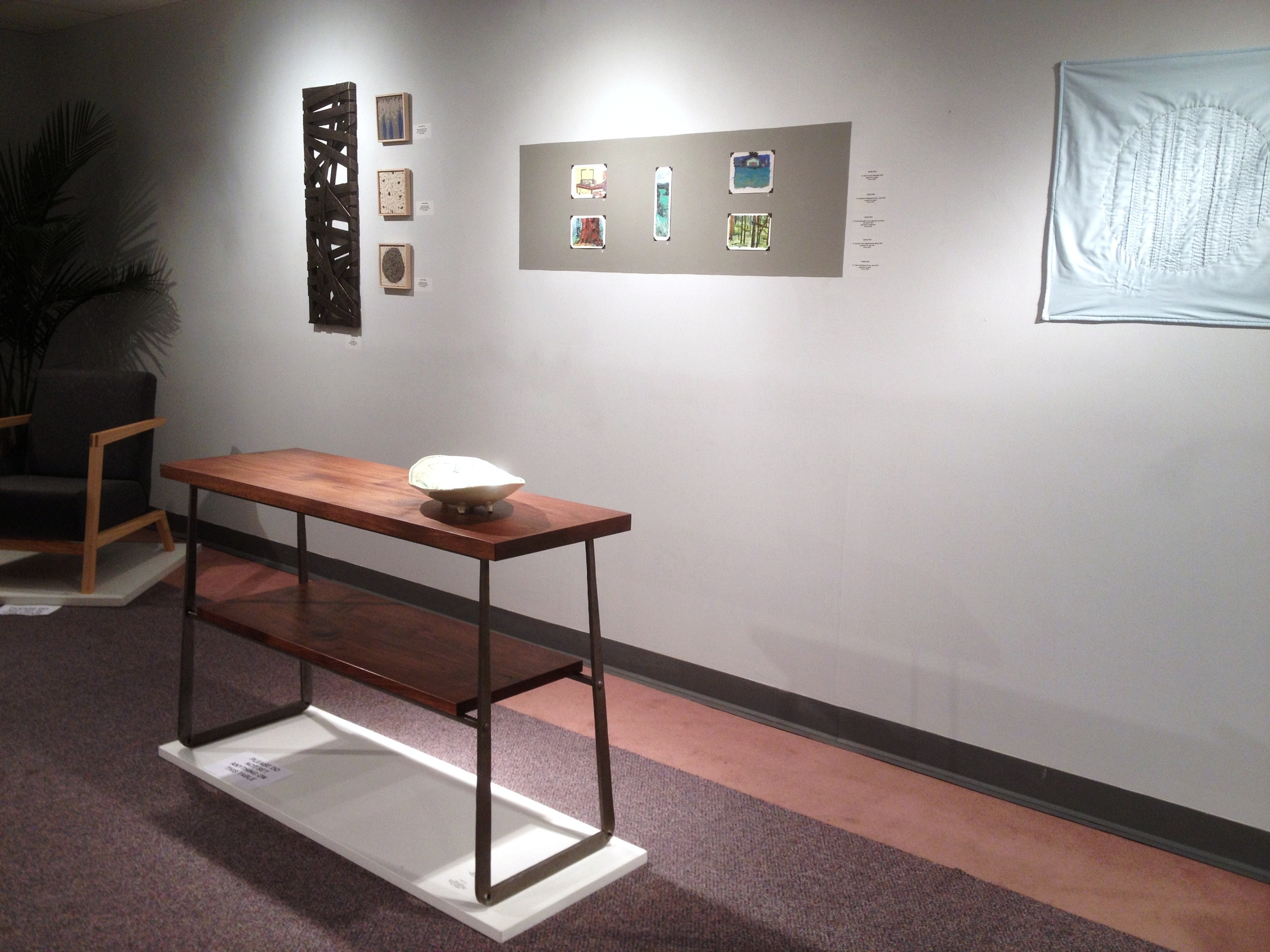 Walnut and forged steel table at group show