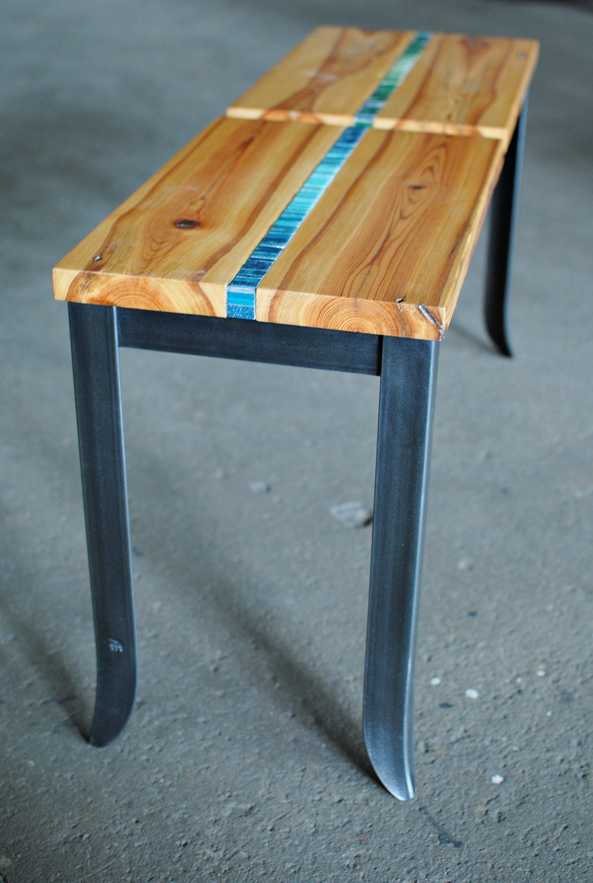 Interior bench with mosaic inlay in wood seats and forged steel legs