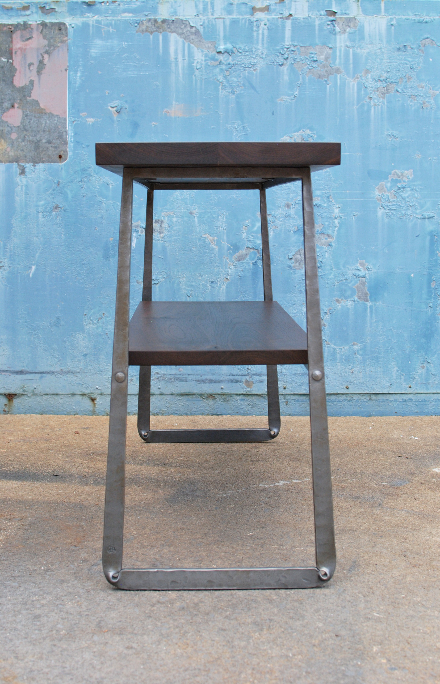 Walnut console with forged steel base, side view