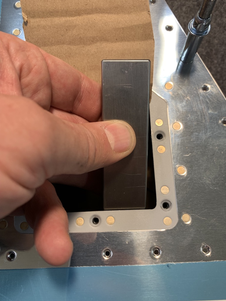 Riveting the trim tab doubler to the 902 front spar. Reaching in with the w-bucking bar.