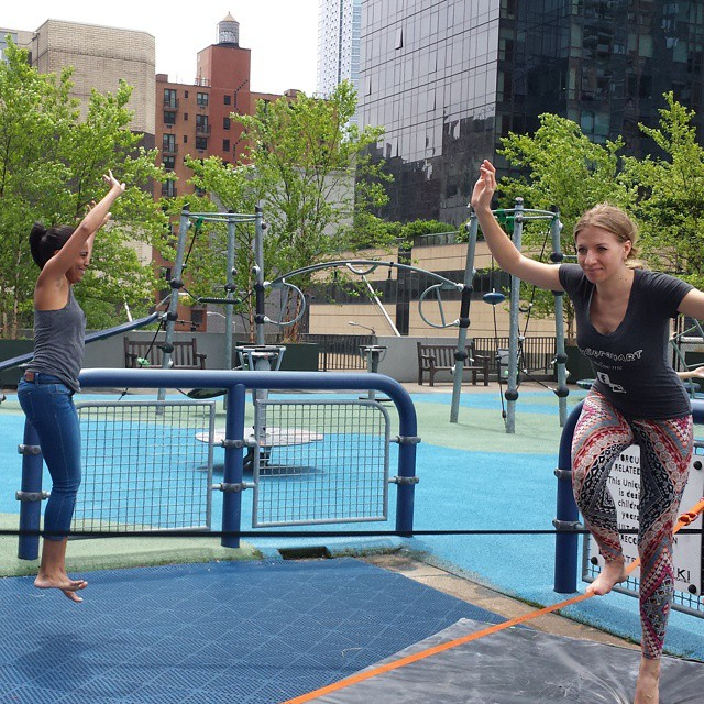 _Slacklining_is_so_much_fun_and_requires_tons_of_balance__especially_when_you_start_from_a_lower_seated_position_and_you_have_to_push_yourself_off_with_one_thigh.__Here__one_person_falls_off_a_slackline_as_another_gets_on_a_separate_slackline_during_.jpg