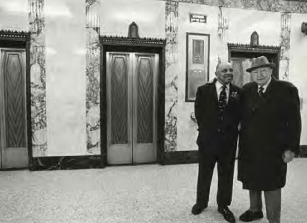 Jimmy Lee visits with an unidentified gentleman near the elevators at the First National Bank Building. Because he was so welcoming to guests and employees, Jimmy was asked to stay as a greeter once elevators became automated. Photo from Lee Family Collection, courtesy of Frank M. White.