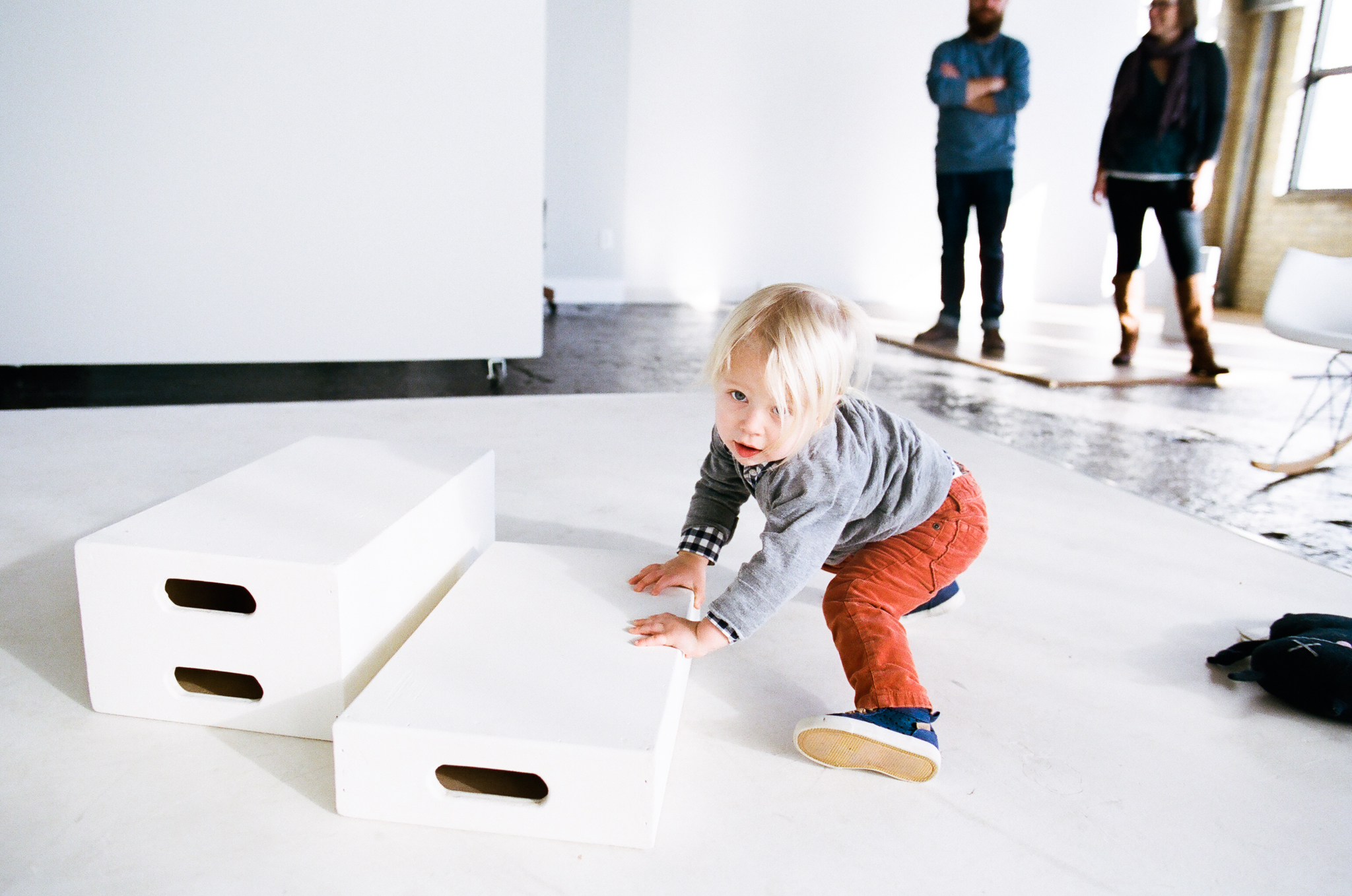 Young boy stacking apple boxes.