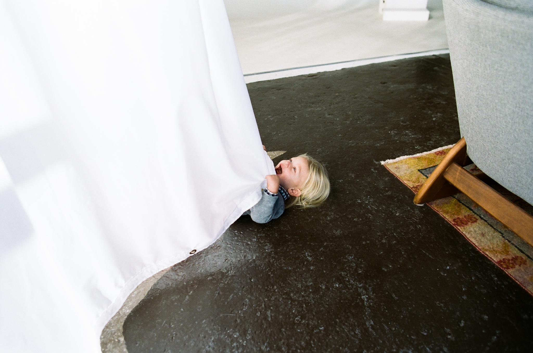 Young boy hiding in a curtain.