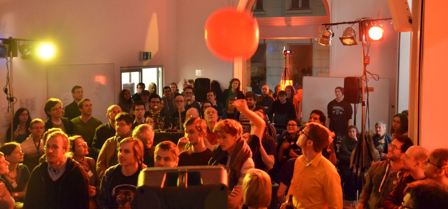 Figure 1 An audience interacts with a balloon during a concert to influence sound effects of a live played piano. (This study was conducted as part of the preceding research project  Wiener Musik-Experimente .)