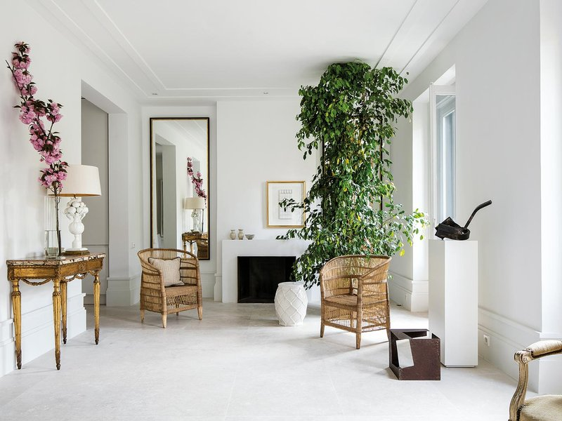 "Interior Designer Miguel García Valcárcel's Madrid home is a study in light, with antiques and contemporary art intermingling with sculptures, ceramics, and wicker, as well as a thriving ficus Peñotes for a bit of green and striking pink cherry blossom arrangements throughout the space keep the palette from being too monochromatic. By removing partitions and opening up the space, García Valcárcel was able to create in this Chamberí district of Madrid space, ""An open, inviting and comfortable for receiving friends home."""