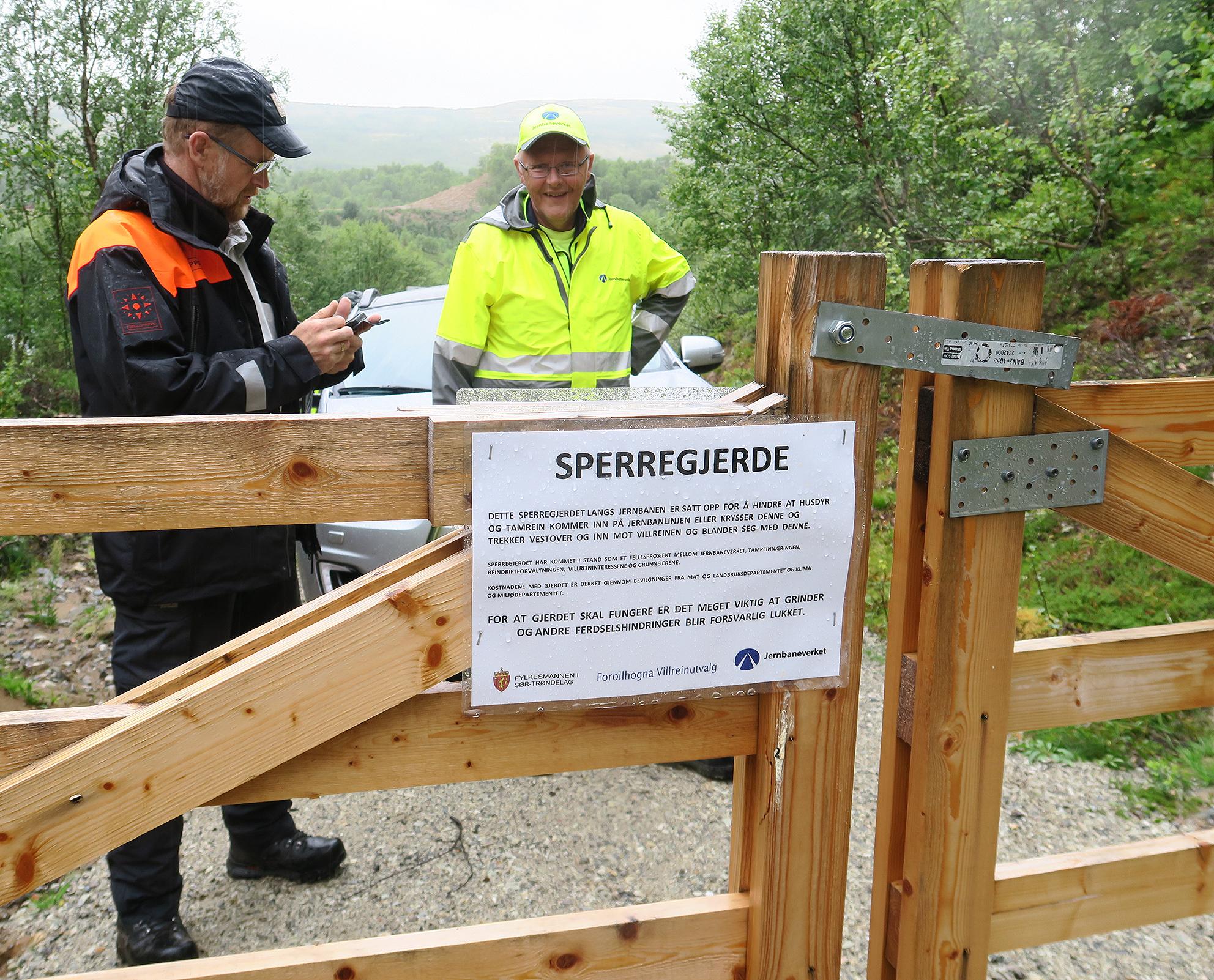 """Det er mange grinder i området. Nå gjelder det å holde disse lukket. På samtlige er det satt opp plakater. Terje Borgos og Jan Einar Moseng fant lite """"å rette pekefingeren mot"""" i dag..Foto: A. Nyaas"""