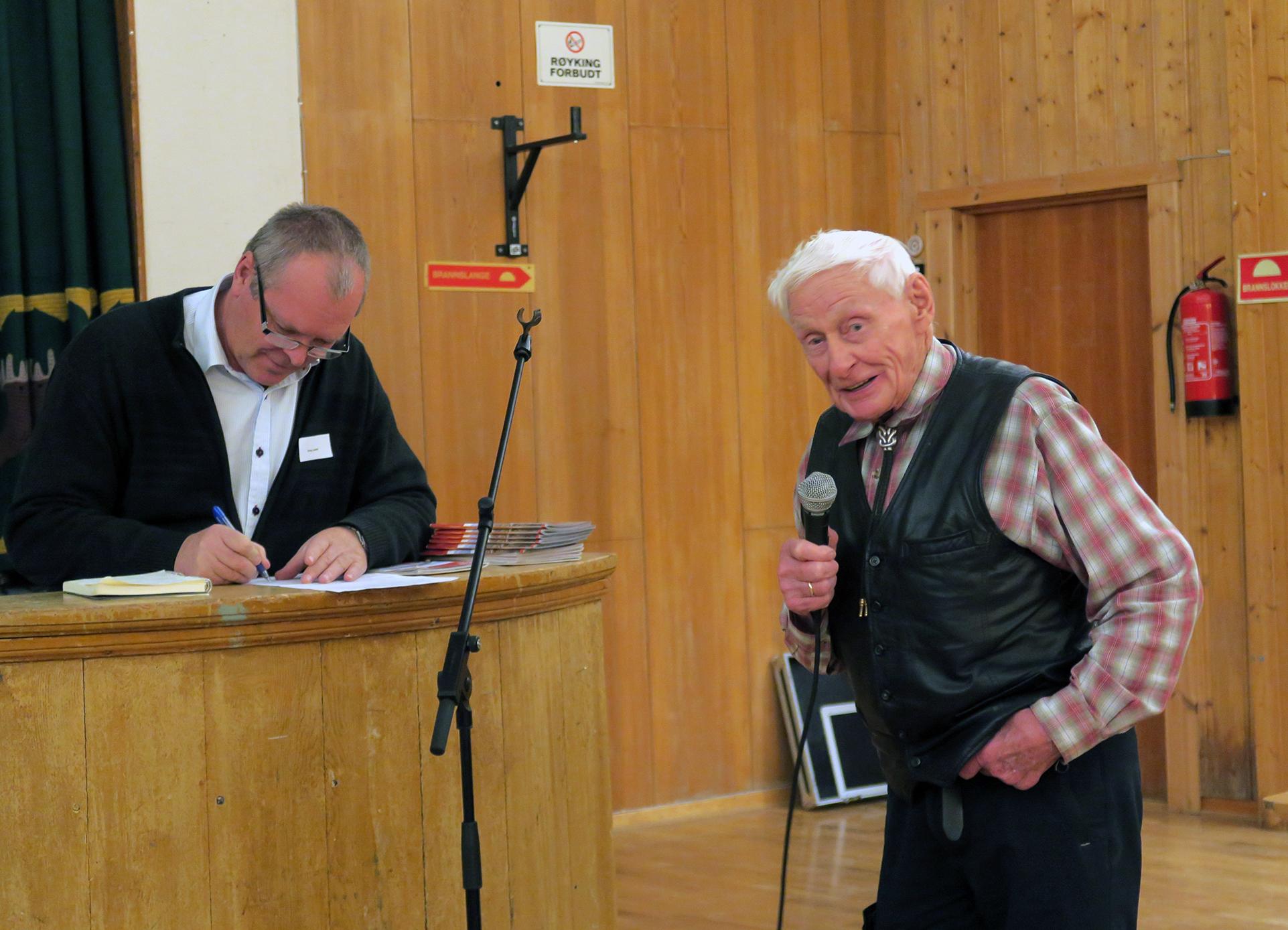 Pensjonert reineier Anders Fjellheim fra Røros grep mikrofonen på Forollhogna-konferansen i Dalsbygda i dag. Erling Lenvik, ordstyrer på konferansen og ordfører i Midtre Gauldal kommune, noterer. Foto: Arne Nyaas