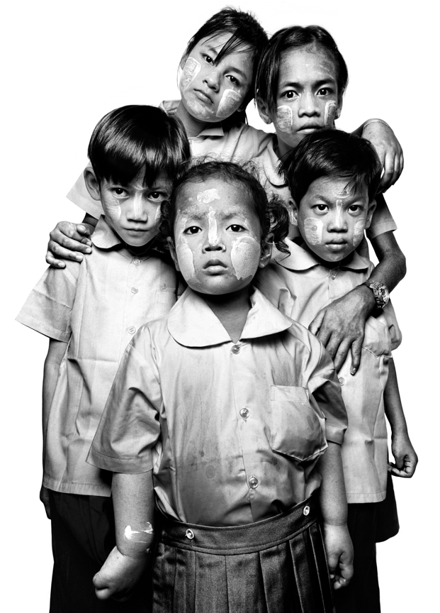 In Burma, the HIV/AIDS medication supply is so limited that only one in four people requiring treatment receives it. These children, who are HIV positive, were orphaned or sent by their parents to Social Action for Women's safe house, the Children's Crisis Center for treatment or protection. SAW provides shelter, education, and basic services for Burmese children including antiretroviral medication. The children wear traditional Burmese tanaka wood paste painted on their faces for protection and decoration.