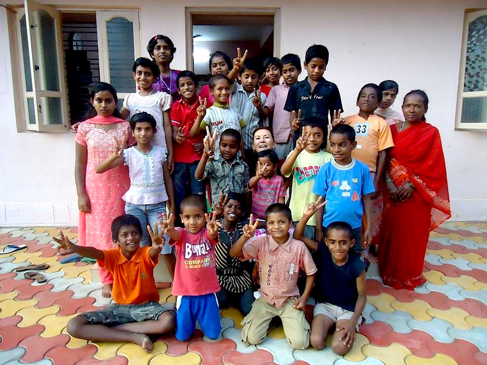 Kids and staff pose for a photo at the Snehalaya Children's Care Centre for HIV-infected orphans in Mysore, India