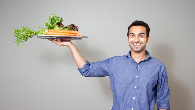 Instacart's CEO poses with a tray of produce.