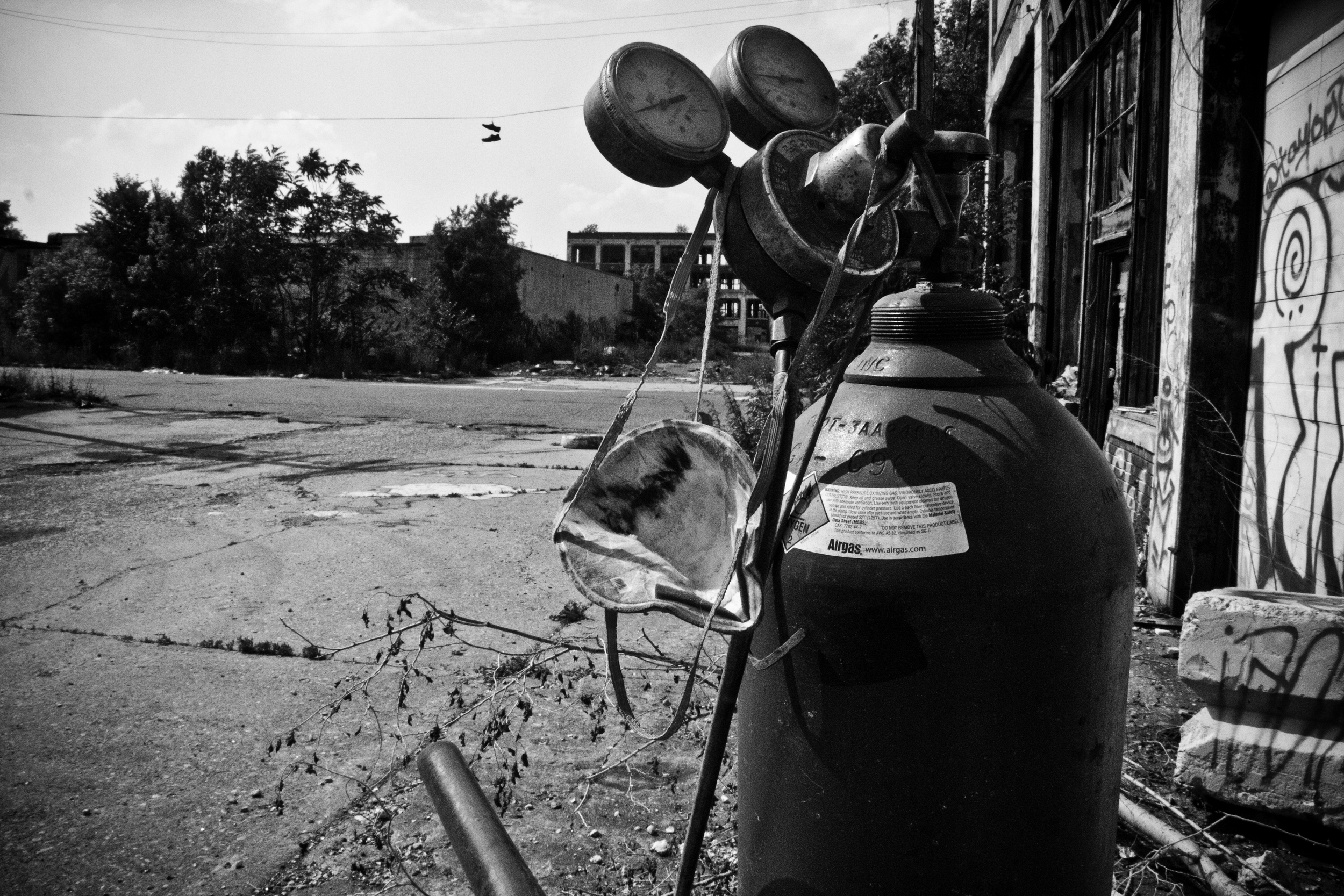 A mobile torch and tank sit outside an entrance to the Packard Plant while a scrapper searches inside for valuable metal.
