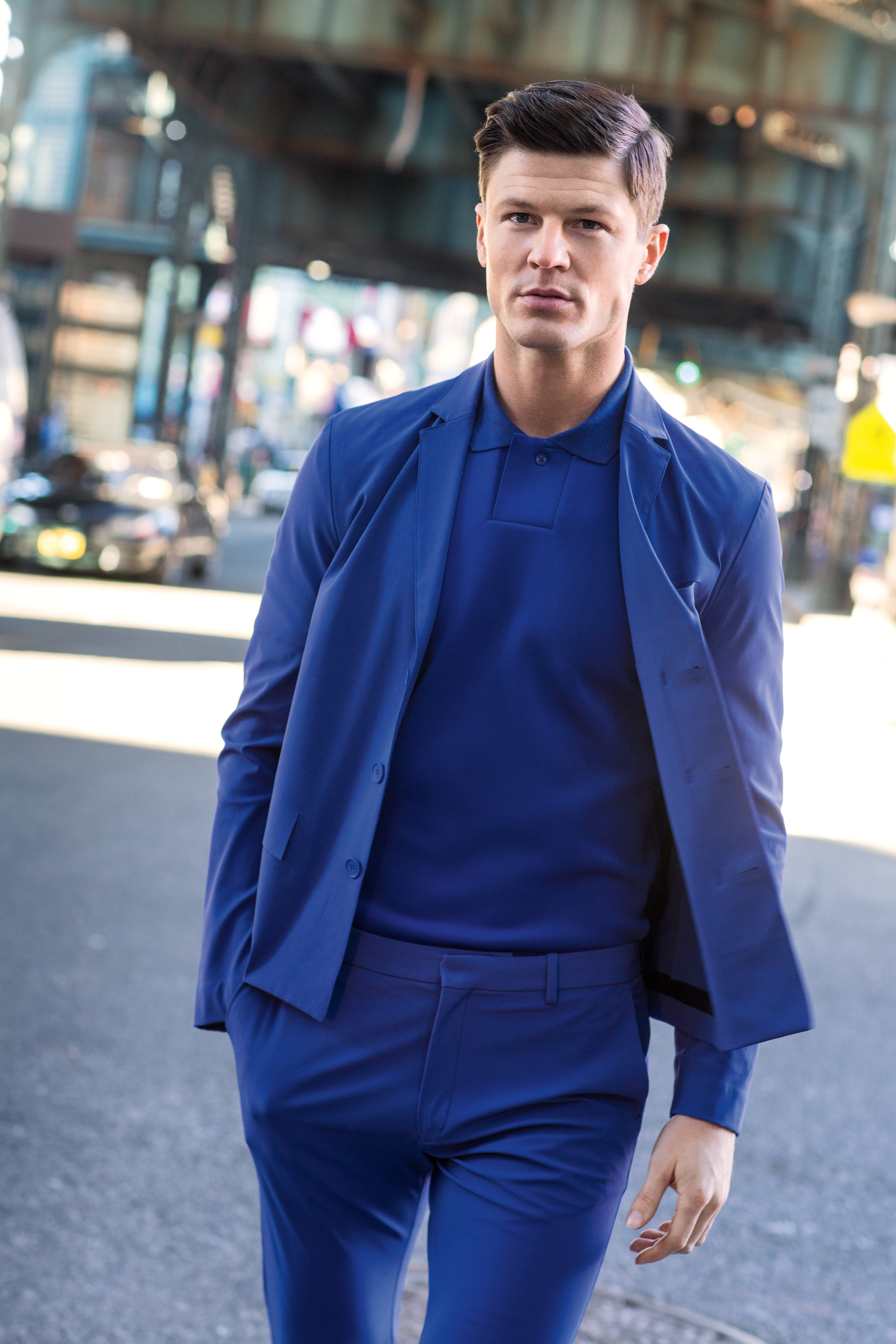 Blake Kuchta   (New York Models)  wears a blazer, polo shirt and pants by Lacoste.