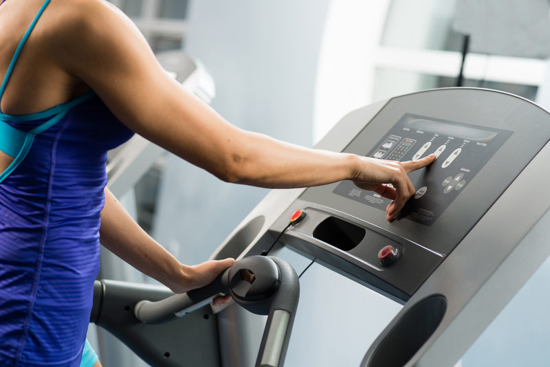 woman-adjusts-treadmill.jpg