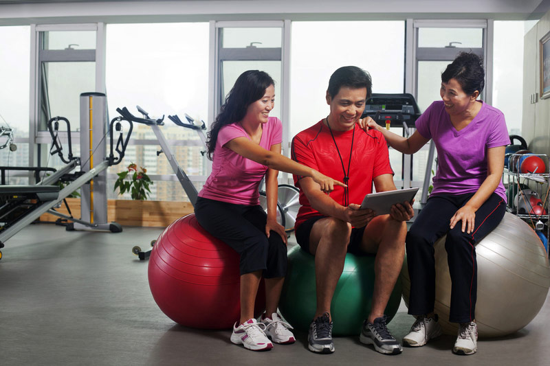group-in-gym-on-exercise-balls-looking-at-tablet.jpg