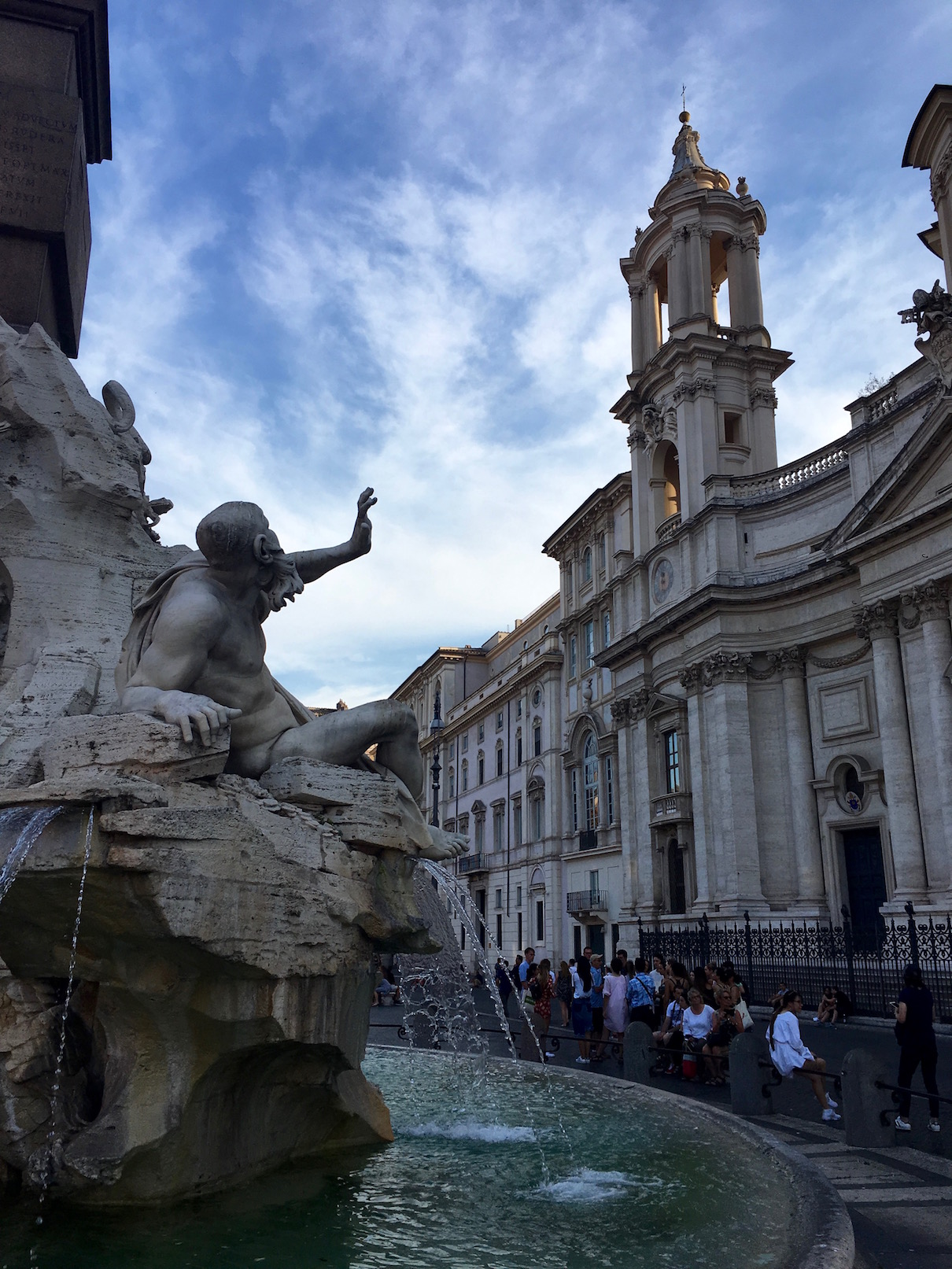 """Our final concert was in Rome directly across from this incredible Bernini fountain in Piazza Navona—the Fountain of the Four Rivers. The """"in joke"""" that I captured here was that Bernini was a competitor with the architect Borromini who was creating the chapel directly across from the fountain. You can see the sculpted figure seeming to recoil from his view of the chapel, as if Bernini is giving his criticism of his competitor. It makes a great story, but alas seems to be apocryphal."""