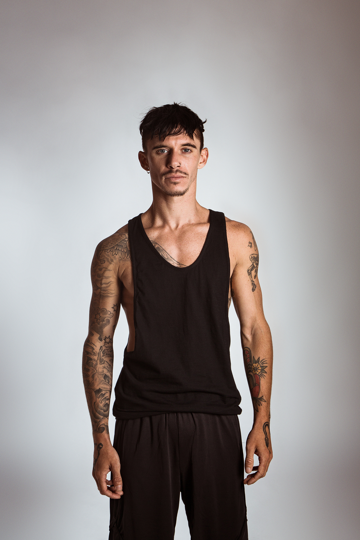 Brad wears the  Men's Cut Away Singlet  and  Urban Short  in Black