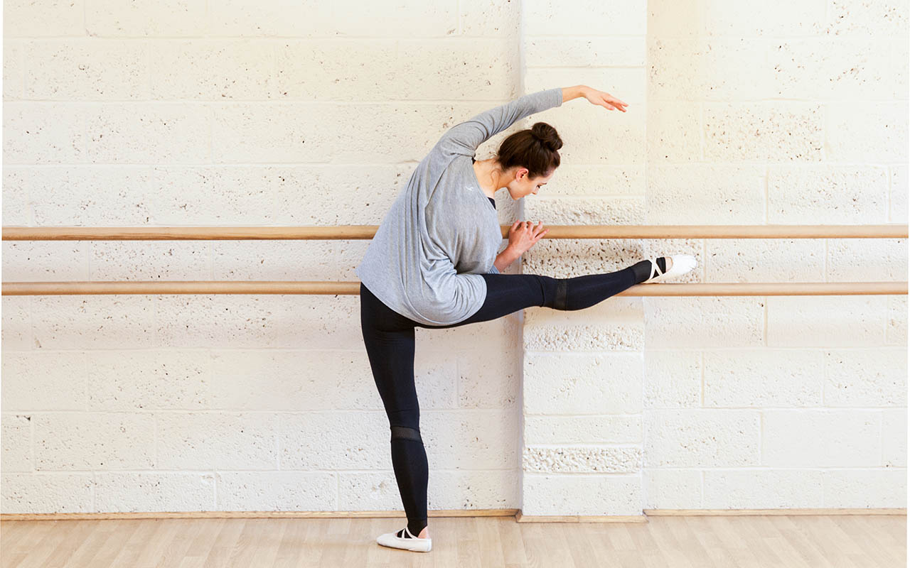 Daisy demonstrates at the barre, wearing the  Zara Extended Mesh Legging  and the  Aubrey Knot Long Sleeve Tee  from the Atelier Collection