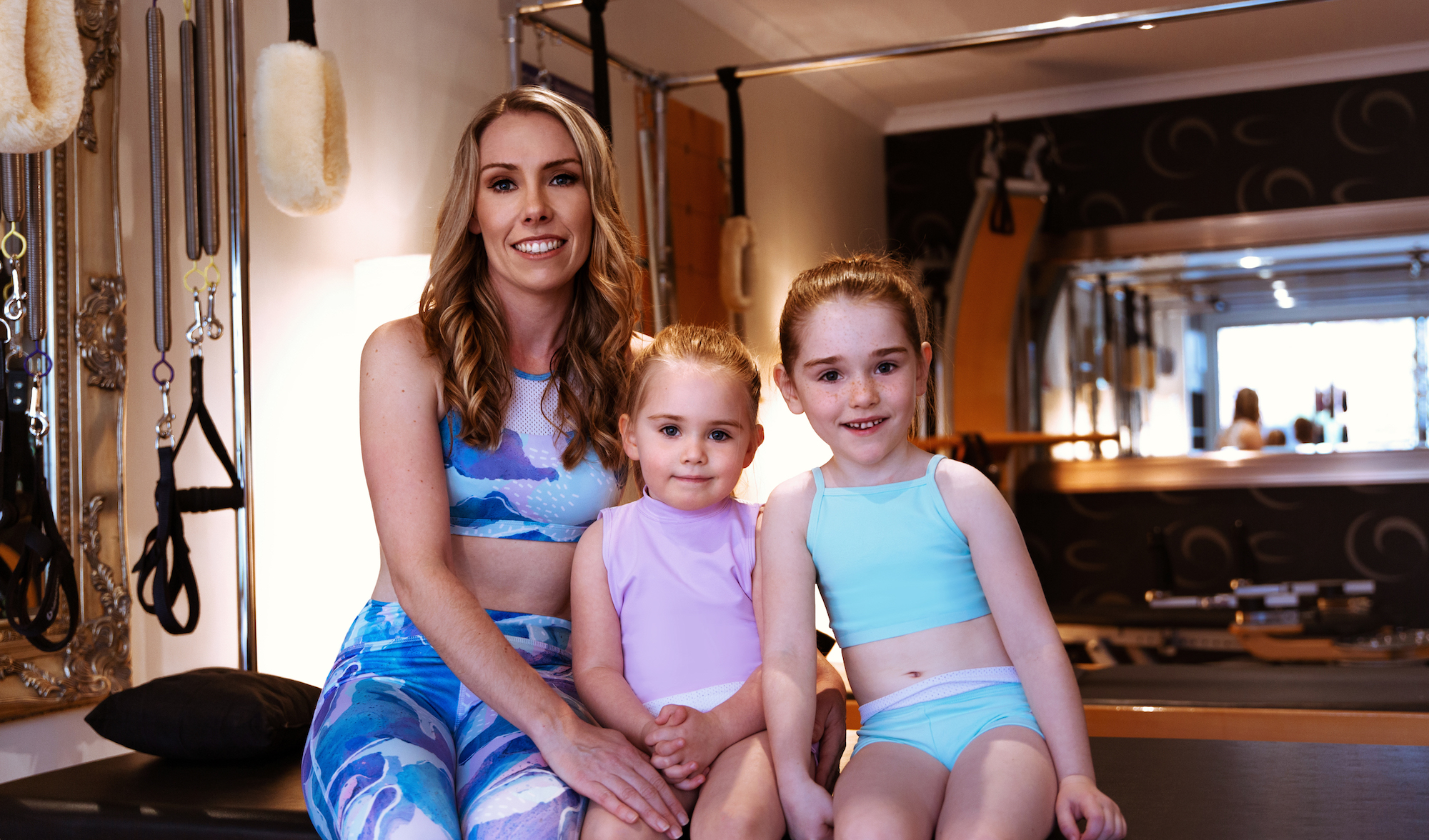 Kate Boyle with daughters Charlotte and Ava in the Energetiks  Moonstone Collection . Kate wears the  Jasmine Crop  and  Lanna 7/8th Legging  in Moonstone, Charlotte wears the  Willow Crop  and  Emily Short  in Lavender, and Ava wears the  Coco Crop  and  Emily Short  in Spearmint.