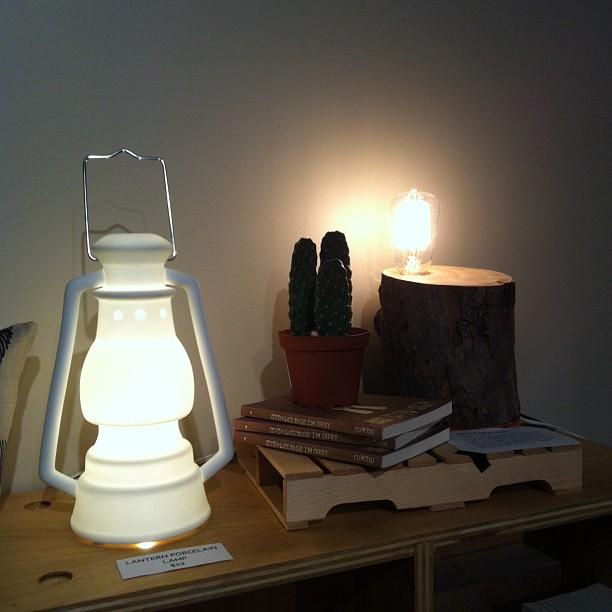 Porcelain storm lantern, $52. Handmade log lamp, $120.
