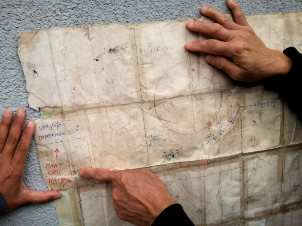 """During one of our visits,Tràn Vân Dũng points out his notes (red color pencil),written underneath the pirate's handwriting (ballpoint pen), which reads,""""you go to Songkhla 250 degrees""""."""