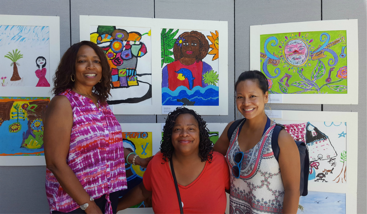 La Verne, Sharonda, and i stand proudly in front of the students' work. In Sheronda's self portrait, Swimming with the Dolphins , they jump out of the water, representing freedom. One of her wishes is to swim with the dolphins in Hawaii, and to have an opportunity to travel the world.