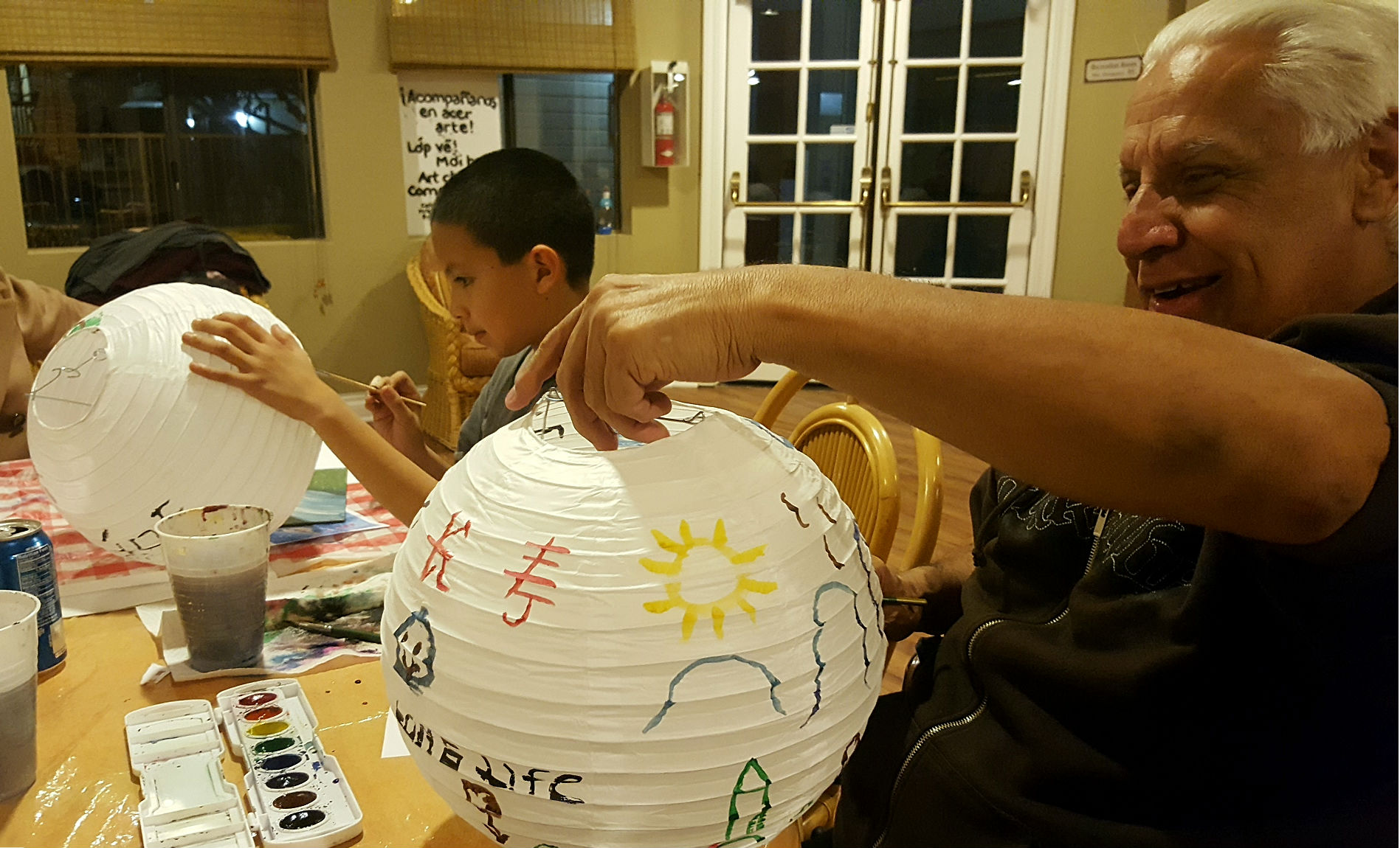 Young Parker and Peter prepare their lanterns for the  Lantern Festival , using traditional Chinese and Vietnamese images of nature. For the upcoming year, Peter hopes for  L  ongevity  and paints its Chinese character on his lantern.