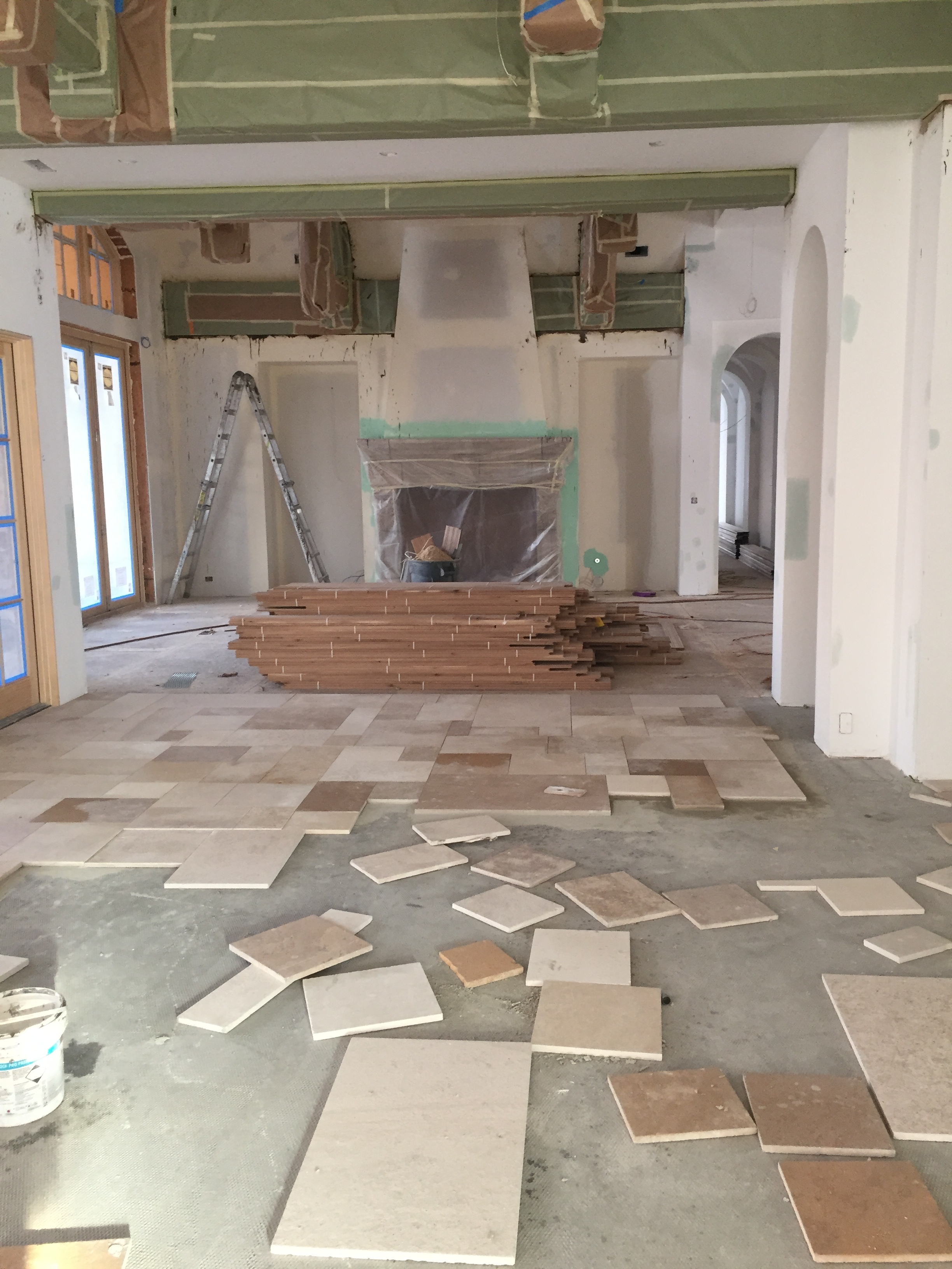 This beautiful antique limestone flooring is what was chosen for the dining room and kitchen. Behind that you can see the piles of wood flooring as it climatizes pre install. The beams were covered and taped off to ensure total protection during construction, as well as the antique fireplace.