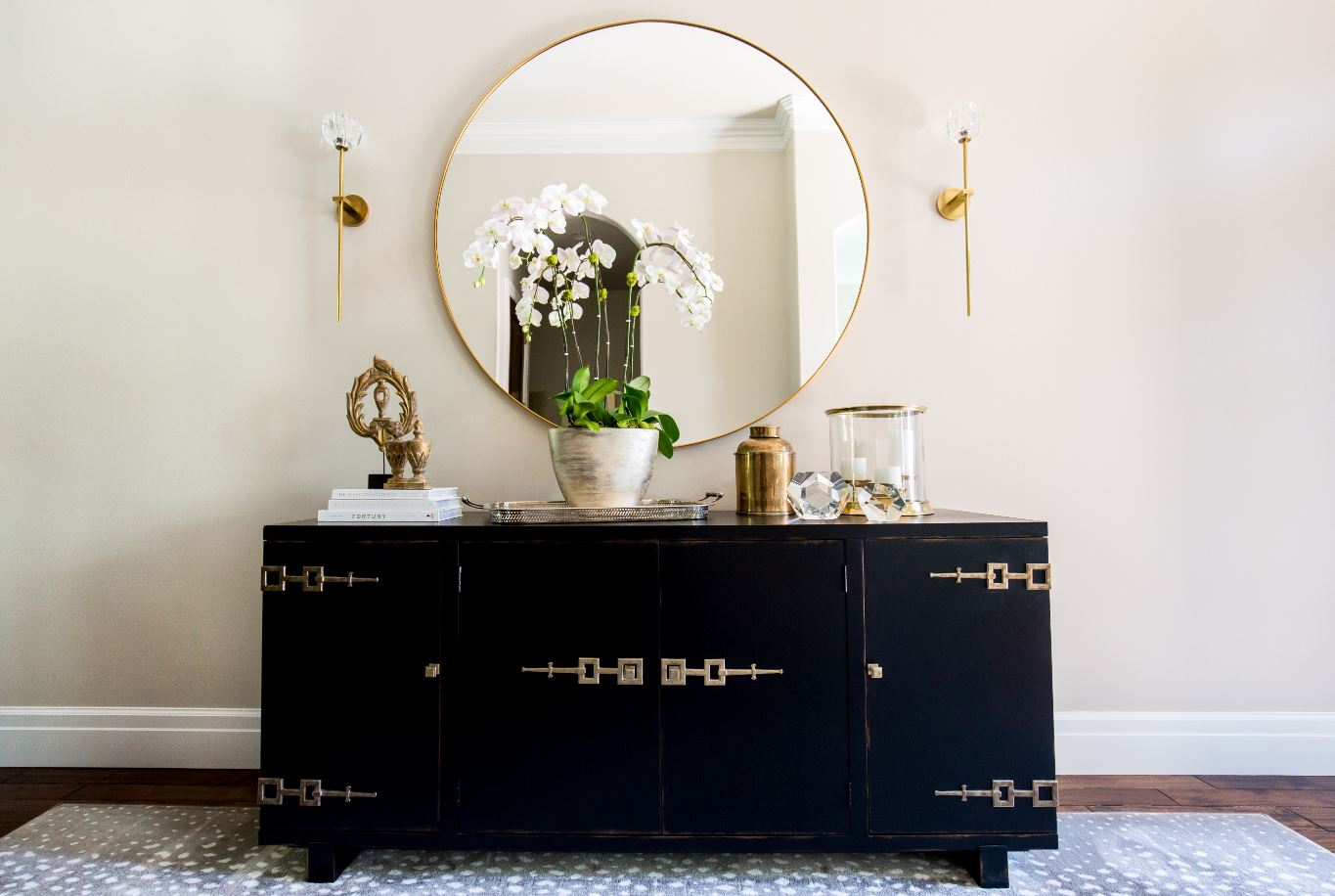 This beautiful sideboard is found in the front entry and we can't get over the gorgeous details! The big round mirror with gold trim was the perfect addition, and we love the delicate feel of the gold sconces!