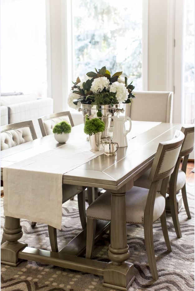 This dining room really has our hearts! The gray table is a solid piece of furniture, but the neutral linens and fresh florals really soften the overall look, making you feel right at home.