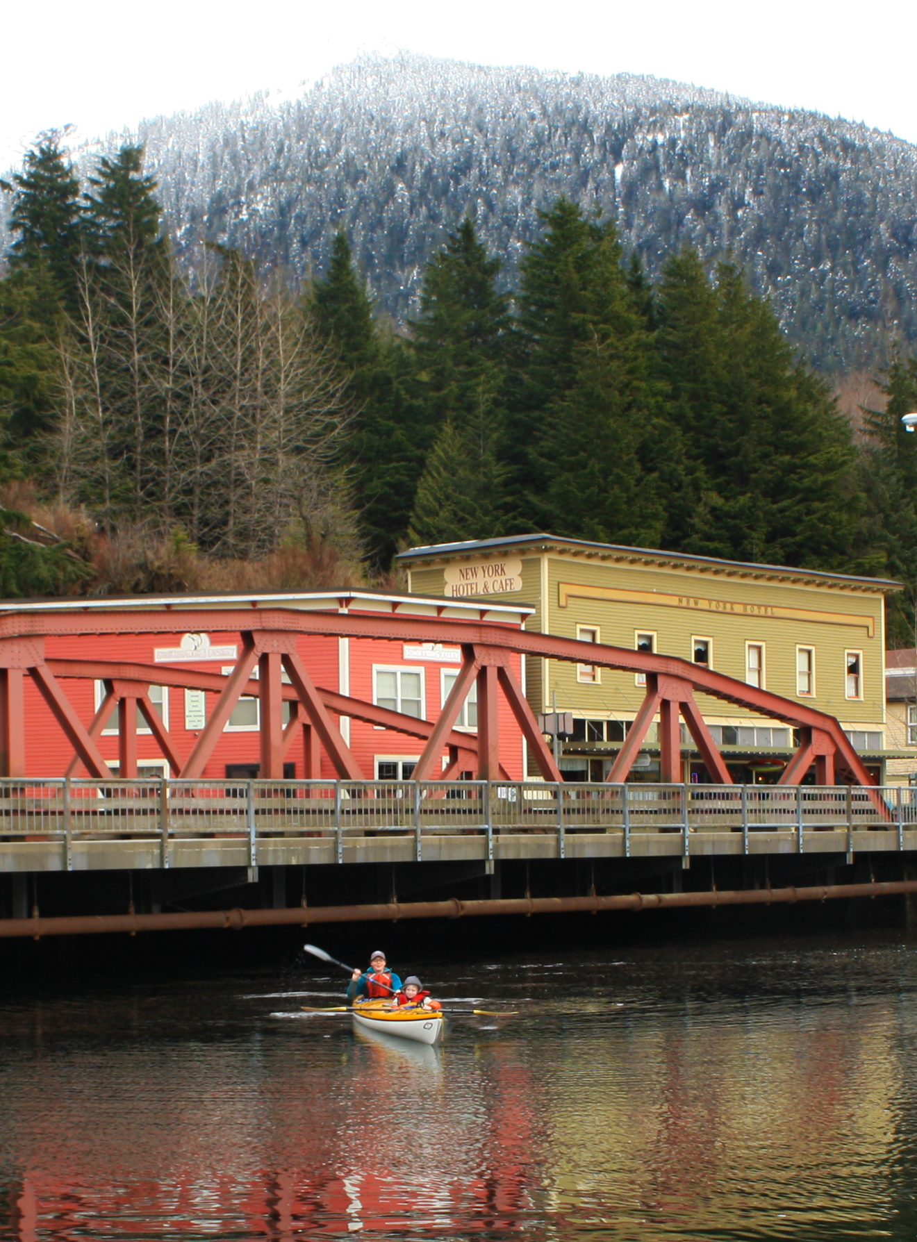 Snow on the mountains and high tide at the Creek Street Bridge in Ketchikan, Alaska