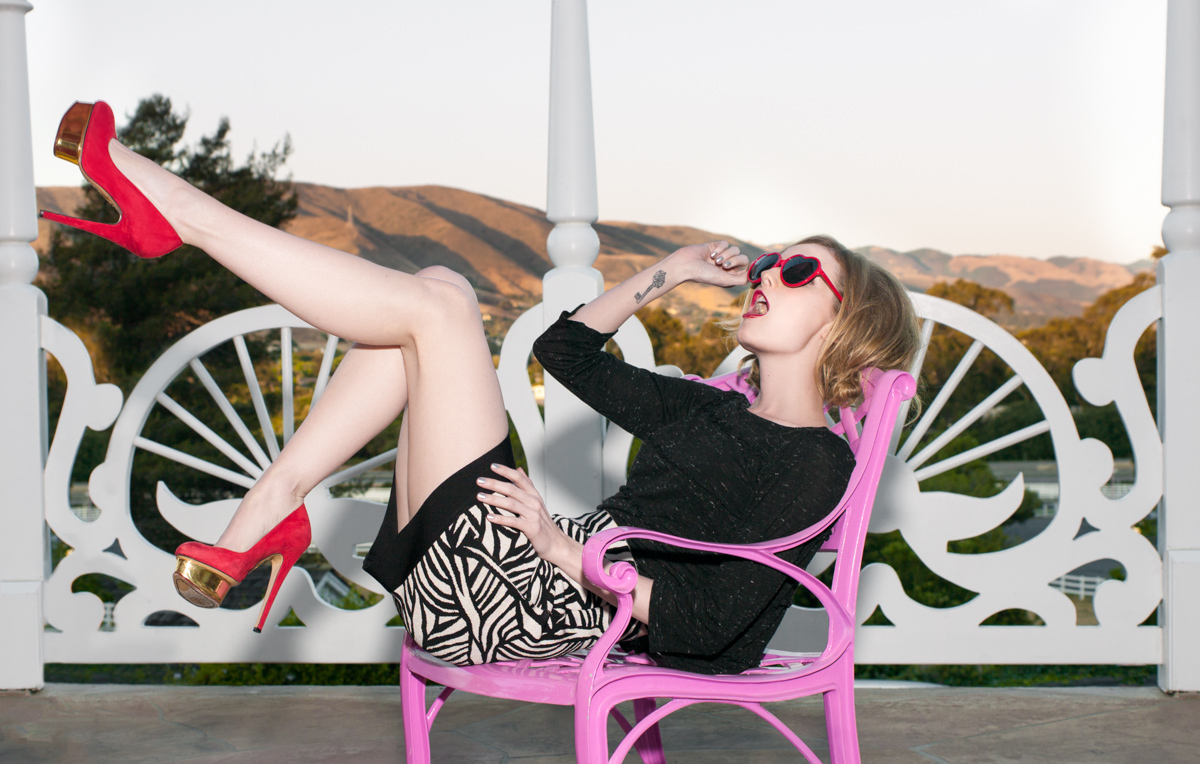 Photographed by  Nadav Benjamin     Hair by  Whitney Olson  Makeup by  Liz Sender      Top :  Marc by Marc Jacobs  – Resort Alice Long Sleeve top in Black $148   Skirt :  Hervé Léger  – Jacquard Bandage Black & White Mini $1,150   Glasses : QLook – Lolita Sunglasses in Red $8.95   Shoes :  Charlotte Olympia  – Dolly Pump Platform in Red/Gold $895  - See more at:  LOVELYDIAHEARST.COM